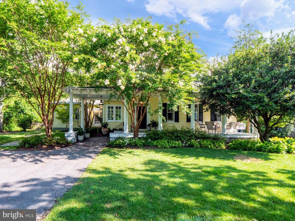 Please view the virtual tour of this extraordinary Southern bungalow, circa 1917. Nestled away from the street amid lush foliage you'll find an unexpected oasis in the heart of one of Alexandria's most coveted neighborhoods. Seated on a picturesque 27,000 square foot lot abounding in perennial plantings, shade trees and blooms, this timeless home offers five bedrooms (including a main level master), three full and one half bathrooms and an extremely gracious flow throughout. From the private driveway you'll pass through the porte-cochère to the peaceful front porch, featuring a swing to lounge and visit as well as a panoramic view of the lovely grounds. Once inside the welcoming foyer you'll feel it: warmth, charm and history, and absolutely nothing cookie cutter. Large spaces for entertaining, three fireplaces, generously sized windows, pocket privacy doors, extensive built-ins, heart-pine hardwoods, a wall of french doors and extensive exterior hardscaping are but a few of this home's attractions. A mudroom, main level laundry room and cozy office/study provide essential space for today's practical living and enjoying more time than ever at home. A wet bar and formal dining room will encourage the entertainer but a bright, sizable kitchen will likely be the spot that attracts the chefs as well as the socializers. The master bedroom, tucked back in a quiet corner, requires climbing no stairs and features a huge walk-in closet and en-suite bathroom with a shower and separate soaking tub. On the opposing side of the home four additional large bedrooms share a quiet upper wing. If you don't need so many bedrooms, utilize the additional space for recreation or another home office, and catch a pretty view from every room. If you're seeking a rear yard with options, you've found it. With a gorgeous tiered patio and expansive lush yard, opportunity abounds. Whether you dream of designing your swimming pool with an accompanying pool house, building an additional studio or guest house, exercising-from-home on your sport or tennis court, or even expanding this already impressive layout, your wish list will finally come to life here. Both indoors and outdoors, at this one-of-a-kind property there's simply something special about every space.