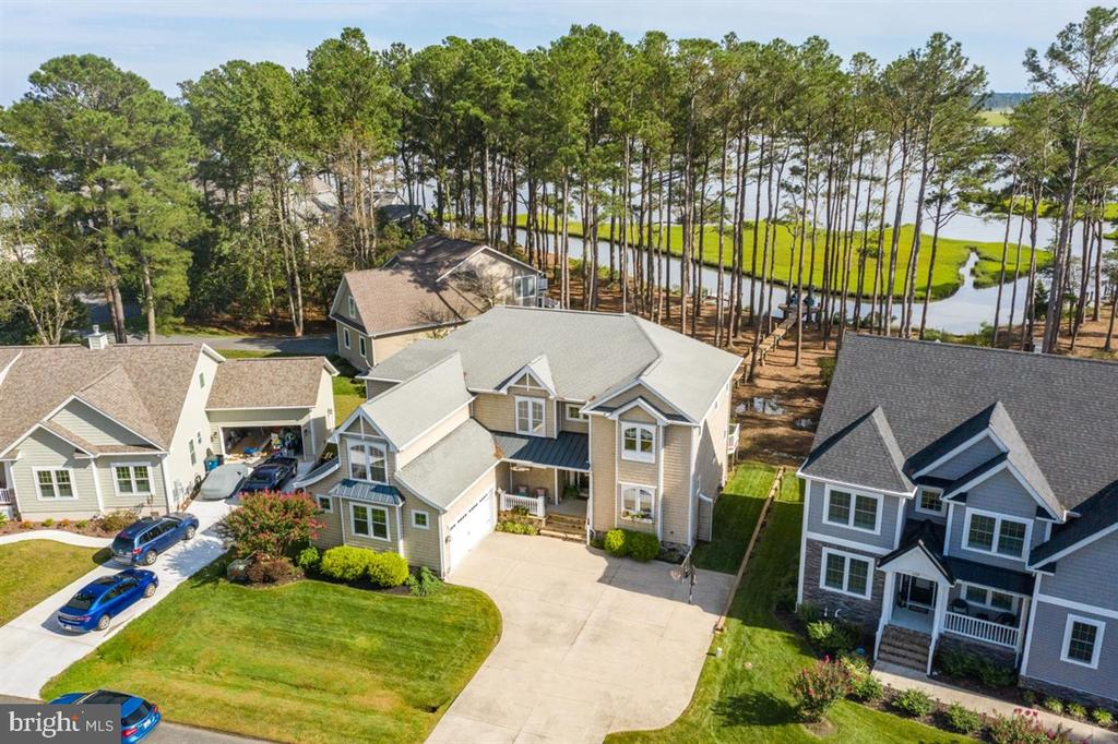 "This gorgeous coastal inspired home was custom built by Heron Bay Builders in 2008. It is located in the desirable ""Point"" section of Ocean Pines. Walk into this home and you are awestruck by serene bay and creek views from a wall of windows. The home features 4 bedrooms and 3.5 baths with a master suite on each level. The home has a desirable open floor plan with great flow. Enjoy the gas fireplace, hardwood floors, and the timeless kitchen with custom 42"" cabinets, granite counter tops, dove tail, soft close doors, stainless steel appliances and a 6 burner Themador gas stove.  Attention to detail continues on the outside of the home with cedar impression siding, beautiful custom river rock  work at the front entry, down-lighting,  an irrigation system, and a side entry 2 car garage. Relax on the upper or lower level deck; the first floor deck is partially screened in and the upper level deck is a sunny oasis. There is a 136' lighted pier and a 10,000 pound lift for your jet skis or boat. Be on the bay in minutes! Bring your kayaks, paddle boards, and fishing rods and enjoy waterfront living at it's finest."
