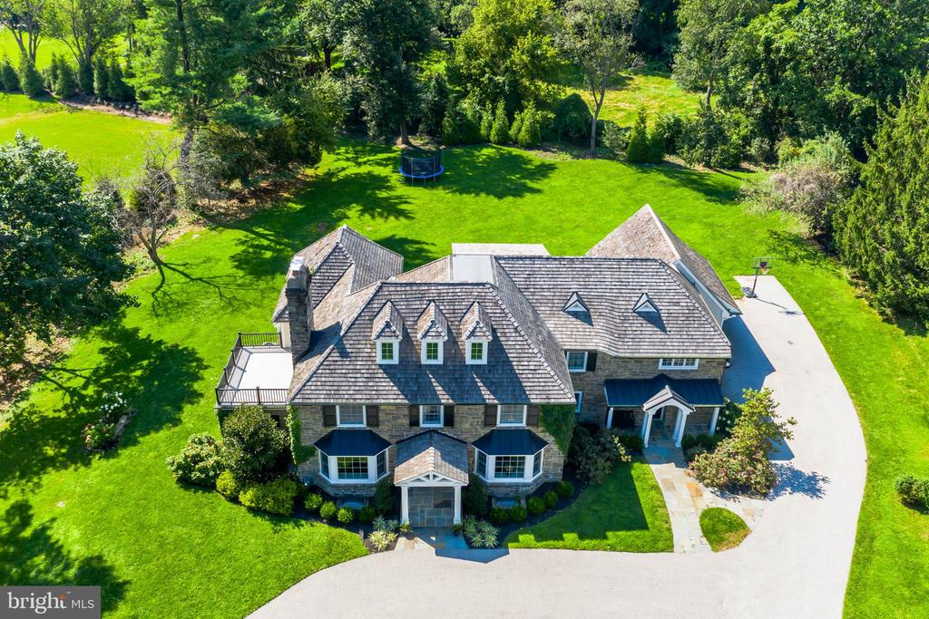 This beautiful Stone Colonial Manor Home is located on 1.4 prime acres in the prestigious estate neighborhood of Merion Golf Manor just steps from Merion Golf Course. The current owners enlisted the help of renowned Main Line Architect; Scott McIntyre of McIntyre Capron & Associates to develop plans for a complete home renovation, gutting it to the framing and foundation in order to convert the more conservative existing traditional layout to open concept living. In 2017, the home won a Synergy Award for best renovation by the Home Builders Association of Delaware/Chester, Berks, and Montgomery Counties.  Several additions to the home were also made adding significant square footage, which includes a great room, master bathroom, master bedroom closets, mudroom, and conversion of a two to three-car garage with living space above. The house has hardwood floors throughout and is filled with beautiful soft light coming from large bay windows at the front of the house that pours into the formal sitting room and dining room, which flank the entrance.  The front entrance leads to a morning room straight through to French doors opening to a flagstone patio ideal for lounging or entertaining guests.  The morning room is open to both the great room and gourmet kitchen.  The kitchen has plenty of cabinet space, Carrera marble countertops, a farmhouse sink, and is equipped with all new appliances in 2017 including a 6-burner Wolf Range with grille, Sub Zero Fridge/Freezer, two Sub Zero beverage drawers in the massive Carrera marble island and a Miele dishwasher.  The butler?s pantry has custom cabinets ideal for wine and glassware storage, soapstone countertops, a wine fridge, and a Scotsman ice maker.  The great room has an open beam coffered ceiling, a stone gas fireplace and large French doors leading to the patio. Stealth Speakers also hide behind drywall providing unmatched cinematic surround sound that is operated via Control 4 as is lighting throughout the kitchen, morni
