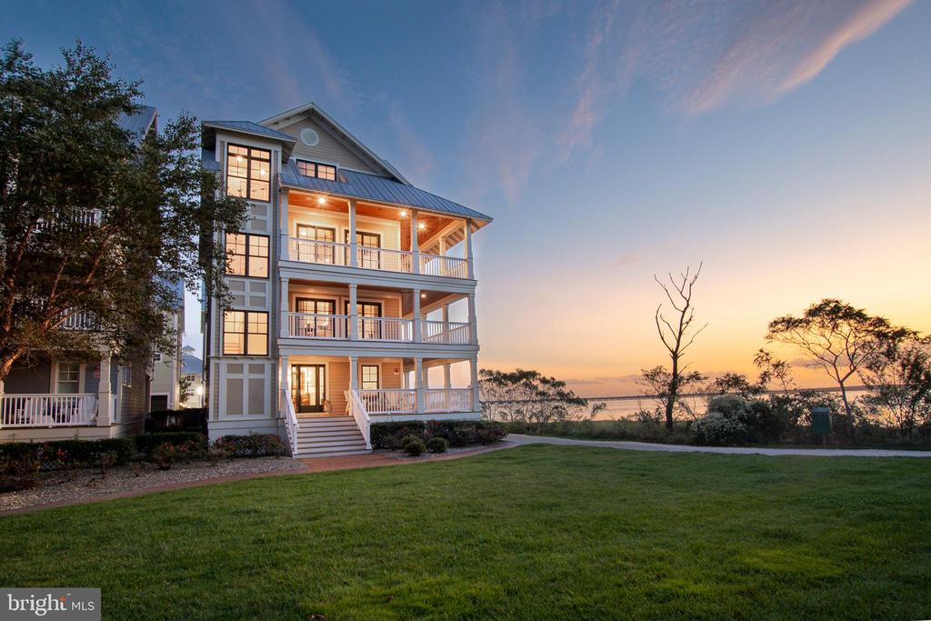 Direct Bay Front single family home with wrap around balconies and views everywhere. Everything about this home screams custom! From the custom garage treatment including a central vac, to the 4th floor rear deck complete with panoramic views of the Assawoman Bay!  The greatest feature of this home besides the exquisite finishes by Main Street Homes, ARE THE VIEWS!  Just 7 Main Street custom homes grace the edge of Sunset Island. Yes, this is one of the magnificent seven. The major customization of this home is the 10' wide plus wraparound decks. These decks allow for panoramic 270 degree views.  The home itself boast the following, outdoor shower, parking for 4 cars and a golf cart, ground floor full bath and den, plus an elevator.  Second floor houses the owner suite and two guest bedrooms with views abound!  Third floor boasts the best views on our island. Great room houses a strategically centered fireplace, with a gourmet kitchen, oversized dining area, and a screen room, with lots & lots of decks and views.  Additionally, there is a butler pantry w/ sub-zero fridge and ice machine.  The forth floor includes a full bath, guest bedroom , and a wonderful second great room leading to a killer rear sun deck.  Upgrades, to mention a few.... Finish in place hardwood floors and steps, central vac, birch cabinetry, bead board,  & over sized trim windows. Plus 80 ft. of  linear deck, 1 year young  oversized washer & dryer, great room with 10 ft. ceilings, granite tops throughout, under cabinet lighting, surround sound, and more! Furniture can be purchased. Agent must accompany all showings. This is a MUST see home!