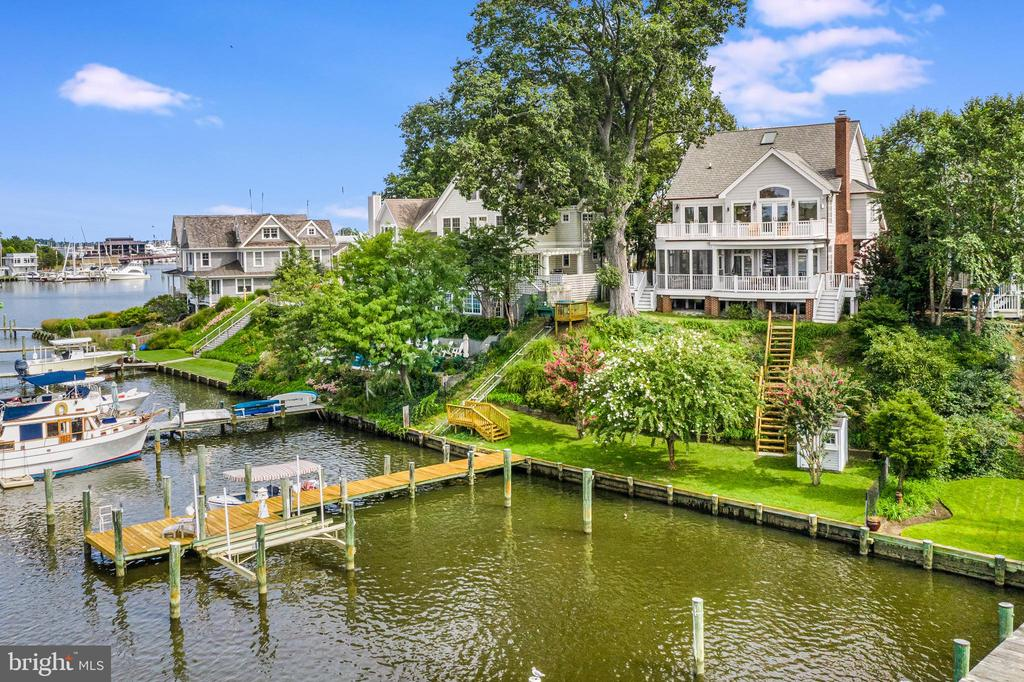 From sunrise to sunset...inspiring water views, majestic herons, bells of St. Mary's and a panorama of historic domes across your horizon.  This elegant waterfront home is the perfect blend of comfortable Southern charm and vibrant coastal living.  Tucked away in a quiet enclave of homes on one of Eastport's most coveted streets on picturesque Spa Creek - the world is your oyster!   With views from nearly every room, several open decks, and a delightful screen porch, this property offers outdoor entertaining space and an unparalleled waterfront lifestyle.  In this quintessential Annapolis home, you can watch graceful sailboats quietly gliding by on a summer night, water taxis coming and going, standup paddle boarders, and small powerboats puttering down the creek. Step from your classic Southern front porch into a grand foyer that opens up to a glistening waterfront setting.  Space, grandeur and light beckon into the elegant but comfortable rooms with warm hardwood floors and tasteful design.  A cozy study offer a wood-burning fireplace and custom built-in shelves.  The open kitchen, dining and living areas, focus on the waterfront setting that will change with each season.  Light a fire in the living room and watch the quiet creek in the winter or open the doors and delight in the summer breezes and sunsets.  The kitchen is outfitted with classic granite counters and the perfect eat-in bar for great entertaining floor.  A main floor bedroom and full bathroom give you flexibility for guests or a back-up bedroom when steps are not an option! Wake up to morning water views from your spacious master bedroom suite.  French doors open to a wrap-around balcony for morning coffee for an evening libation.   The master bath suite features marble floor and vanities, walk-in closet, soaking tub with separate shower, and a coffee station/wet bar.  A small room that adjoins the master bedroom can be used as an extra guest room, office, or sitting room.  The second floor also features a guest bedroom with adjoining boutique bath/shower and a laundry room.   Distinctive highlights and upgrades to this house include custom crown moulding, custom fireplace mantels, newly refaced kitchen cabinets, Casablanca ceiling fans, refinished hardwood floors, copper gutter and downspouts and a superior sound system with speakers on the outside decks and most rooms.  The property has two deep water boatslips, a boatlift and 83 feet of waterfrontage that is protected with recently improved bulkheading.  There is a tram to carry people and boating gear from the backyard down to the waterfront, new stairs, and a boat shed for boating supplies and garden tools near the dock.  Out your door and down the steps - and you can be crabbing, fishing, kayaking, paddle boarding, sailing or powerboating or heading out by boat to restaurants or visiting friends by boat on the creek. With a premium location in Eastport and a home that is perfectly designed for waterfront living, relaxing and entertaining - this home has it all.  Close proximity to local restaurants, maritime museum, yacht clubs, and downtown Annapolis.  Seasonal water taxi pickup at your dock for drop off at City Dock and waterside restaurants. This is urban living on a quiet street with a fabulous waterfront scene that will delight from morning to night.  This house offers a front row seat with an historic backdrop in one of America's top, small waterfront cities.
