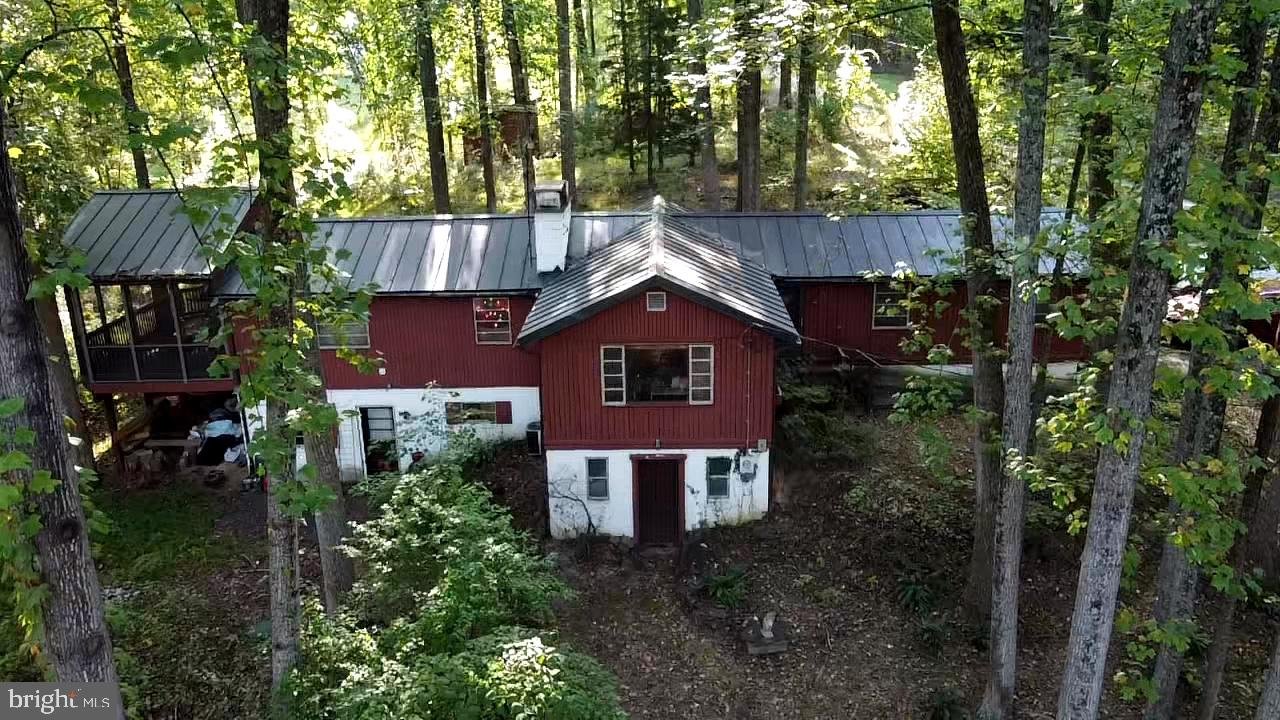 "Multiple offers in hand. Please present offers by Thursday, January 14, 2021 by noon.  Property listed AS IS. Thank you  Serenity! Welcome home to 15 Big Bear Lane in historic Harpers Ferry, West Virginia!  This is one of the original Belair ""Stockade Style"" log homes built in Shannondale in approximately 1955.  This ranch style home had a large addition completed in the early 1970s.  It is a nature lover's dream and the seller has maintained the grounds organically for 19 years.    The main floor has approximately 1800 square feet with two bedrooms and a full bathroom.    The main living area shows the immense character of this charming log home with wood walls and ceilings.  The wide pine plank floors have withstood the test of time and remain a true enhancement of this space.  Natural light flows readily through the large windows that span the family room.  Cozy up next to the large stone fireplace and hearth to enjoy the 1+ acre wooded surround.  A  large, finished space and a full bathroom are located on the basement level.  Along with the full bathroom the basement also has two utility sinks and walk out entry to the back parking space. The metal roof was installed in approximately 2009 along with a new septic system just a few years ago.  Enjoy a nearly 360 degree view of nature from the front and rear decks, along with the expansive side screened-in porch.    This nature lovers retreat is just a short walk/drive to a path leading to the Appalachian Trail.  Enjoy the 3 mile loop around Shannondale Lake or a drive to the nearby public boat ramp access to the Shenandoah River. Bonus: included with this nearly 1 acre lot is the adjoining 0.2579 acre parcel. The home is being sold as is, with a few updates this could be your weekend retreat or forever home!"