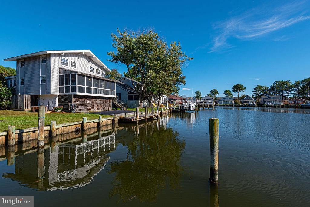THERE'S ROOM FOR EVERYONE in this Teal Bay Waterfront Home with Direct access to the Saint Martins River!  Wide Views of intersecting canals!  Five Bedrooms (One has no closet), huge, sunny Dining Room, Eat-in Kitchen, Screened Porch and Front Deck.  Extra large  ground level rear Deck and private Boat Dock.  The bottom level offers an abundance  of secure storage, almost like having a double garage! Both baths have been nicely updated.  All upper level bedrooms feature brand new carpeting, vaulted ceiling, crown molding, and exposed beams.   Wood burning fireplace, waterfront bedroom & brand new plank flooring through the main level. The perfect getaway!!