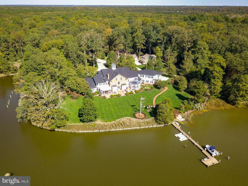 Extraordinary waterfront estate between Easton and Oxford on Peachblossom Creek provides a commanding presence with southern exposure, high elevation, mature trees and a private setting.  Built in 2004 the residence and improvements bespeak quality, and it shows with attention to detail in every facet.  From the manicured grounds to the immaculate systems and infrastructure of the house, this offering is sure to please the most discerning buyer. A grand entry with two story foyer and gallery sets the tone upon entering this magnificent home.  The trim work, joinery and finishes are immaculate and spaces within the residence are proportionally balanced creating an extremely comfortable and inviting atmosphere.  From the first floor master suite, library, office, media room, formal living & dining, transverse hall, kitchen and casual living space / atrium clad in windows from floor through the ceiling, au-pair suite with kitchen, living and bedroom, oversized garage, gun & rod room, dog wash station, full 6,000 square foot basement with an exercise room and wine cellar to the second and third floors including billiards room, elevator and five guest suites, this residence is remarkable.   The guest / caretaker's cottage is a short remove from the residence with screened porch, open living / kitchen, two bedrooms upstairs and a full basement and detached two car garage. Additional property improvements include a utility barn, two docks, one with a unique deep-water basin as well as a boat house, boat ramp, cove-side firepit / patio and extensive landscape lighting and hardscape.   The offering of the house, guest house and accessories on 10 acres is complimented by an additional inland parcel across from the driveway entry.  This additional 2-acre parcel is included in the sale, Tax ID 2101085166.  Proximity to Easton - 6 miles, Oxford- 7.5 miles, Philadelphia - 116 miles, and Washington D.C. - 75 miles puts this offering in a very desirable location enjoying a rural, s
