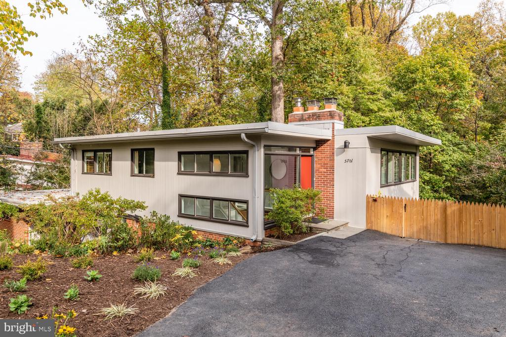 """This mid-century modern """"upside-down"""" house in the coveted neighborhood of Somerset is unlike any other. Designed in 1950 by renowned female modernist architect Chloethiel Woodard Smith, the house features floor-to-ceiling windows and views from all rooms of the ever-changing landscape of adjacent parkland. Watching the deer, foxes, owls, chipmunks, and array of songbirds, you will  almost forget you're walking distance to Friendship Heights metro and Whole Foods. Located a block from Somerset Elementary and the Somerset town pool, this 6-bedroom, 2.5 bath nearly 2,700 square-foot gem was completely renovated while retaining its original mid-century vibe.    The upper level foyer is flooded with light. The main bedroom has floor-to-ceiling windows facing the park and an adjacent bedroom/study has a brick fireplace. Two additional bedrooms on this level are located in a separate wing. Two sparkling new bathrooms feature high-efficiency plumbing, lovely marble and glass tilework, and a modern soaking tub.  After descending the elegant wood-paneled stairway you are immediately struck by the expansive view of the perennial garden and forest from all directions. The large living room features windows on three sides and opens to an expansive slate and brick patio. The original owners, Washington Post Business Editor, Hobart Rowan, and his family hosted many parties for well-known Washington guests in this home, which was clearly designed for entertaining.  The current owners updated the lower level to include new underfloor radiant heat and mini-split heat pumps for multi-zoned air conditioning. A sparkling new open-plan kitchen includes a Thermador gas stove, an Advantium Speedcook oven, a two-column refrigerator and freezer, all-white cabinets and countertops, and designer lighting. The adjacent dining room includes a wall of mahogany cabinets for storing your extensive china collection and a marble buffet is also built-in. Off the kitchen, there is a half bath and a mu"""