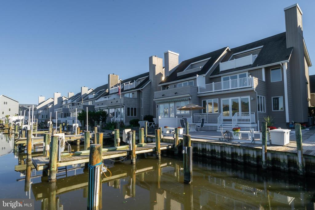 Spacious luxury townhome with direct waterfront access in Ocean Pines, MD. Located on a wide, deep canal in Ocean Pines, this 4-bedroom, 4/1 bath home is laid out over 3,172 sq ft. This home features a cleared bulkhead, dock, and a boat slip with a lift ideal for the boating enthusiast. The interior features a Fireplace and Wood Floors. There are two primary bedrooms. The first primary bedroom includes an ensuite bath, jacuzzi tub and deck access. The second primary bedroom also features an ensuite bath and deck access. The kitchen is open with a Down Draft Cooktop and Wall Oven/Range. The home is directly across from a park. Community amenities include a Beach Club, Boat Ramp, Club House, Golf Course, Marina Club, Outdoor Pool, and Tennis Courts. 2 car garage.