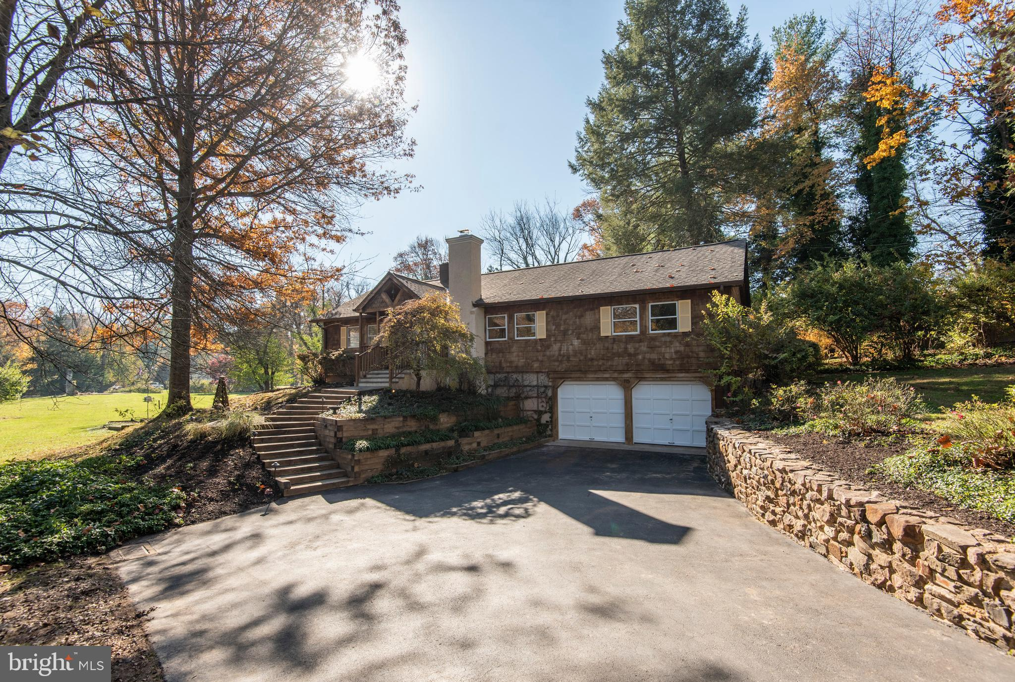 Looking for a property that will provide many years of in-home enjoyment? This ranch style, heart throb of a home will provide just that! Imagine cold Winter nights soaking in the hot tub on the multi-level deck while star gazing and sipping wine. Or preparing meals in a newly remodeled kitchen! This home is located on a beautiful lot just moments from King of Prussia, Downtown Wayne and convenient to Center City Philadelphia. You will love the charming wood facade and covered front entryway that leads into the foyer. The living room with wood floors and crown molding is warmed by a gorgeous brick fireplace. The dining room provides an intimate environment with chair rail, crown molding and modern light fixture that adds ambiance while entertaining. The stunning and spacious kitchen has an abundance of white wood cabinetry and tons of counter space to prepare wonderful home-cooked meals. It also offers granite counter tops, tile back splash, white wood flooring, stainless steel appliances, 5-burner dual fuel stove with oven warming drawer, double bowl stainless steel sink, greenhouse window over the stove, and French doors that lead to the deck. The kitchen is open to the family room (formerly the third bedroom) with an abundance of natural light illuminating both these spaces. You will love the main bedroom with crown molding and four closets (one closet has double hung rods and another features a wooden closet organizer). The guest bedroom has a closet and could also be used as a quiet first floor office or study. Both bedrooms provide convenient access to the  graciously appointed full bath. Wooden stairs lead to the lower level with a brand-new powder room with tile floor. You will also find access to the laundry room and the 2-car garage. It provides another room that could be finished into a home office, GYM, recreation area, etc. The possibilities are endless! The exterior gives both privacy and comfort, with views of a babbling creek and gardens from the lar