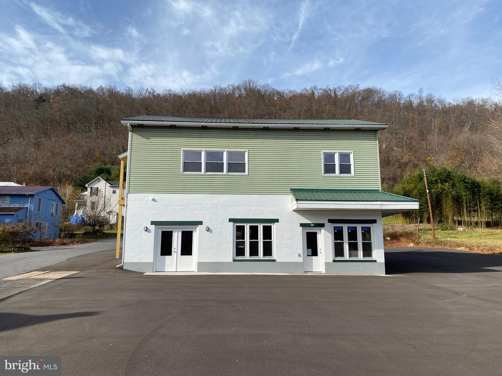 LOCATION, LOCATION, LOCATION  -   This totally remodeled building fronts busy US Route 522 in downtown Berkeley Springs.   The main level could be perfect for your business.    1200 square feet of space includes 12x28 office space, 24x28 showroom  and ADA compliant 1/2 bath.   The upper level features a 1200 square foot apartment with 2 bedrooms, 1 bath, kitchen - dining room and large living room.   Each unit has its own heat pump and electric service.  Public water, sewer, hot water heater are shared.    Large paved parking lot for your potential business.    .13 acre sitting on the corner of US Route 522 & Depot Street.