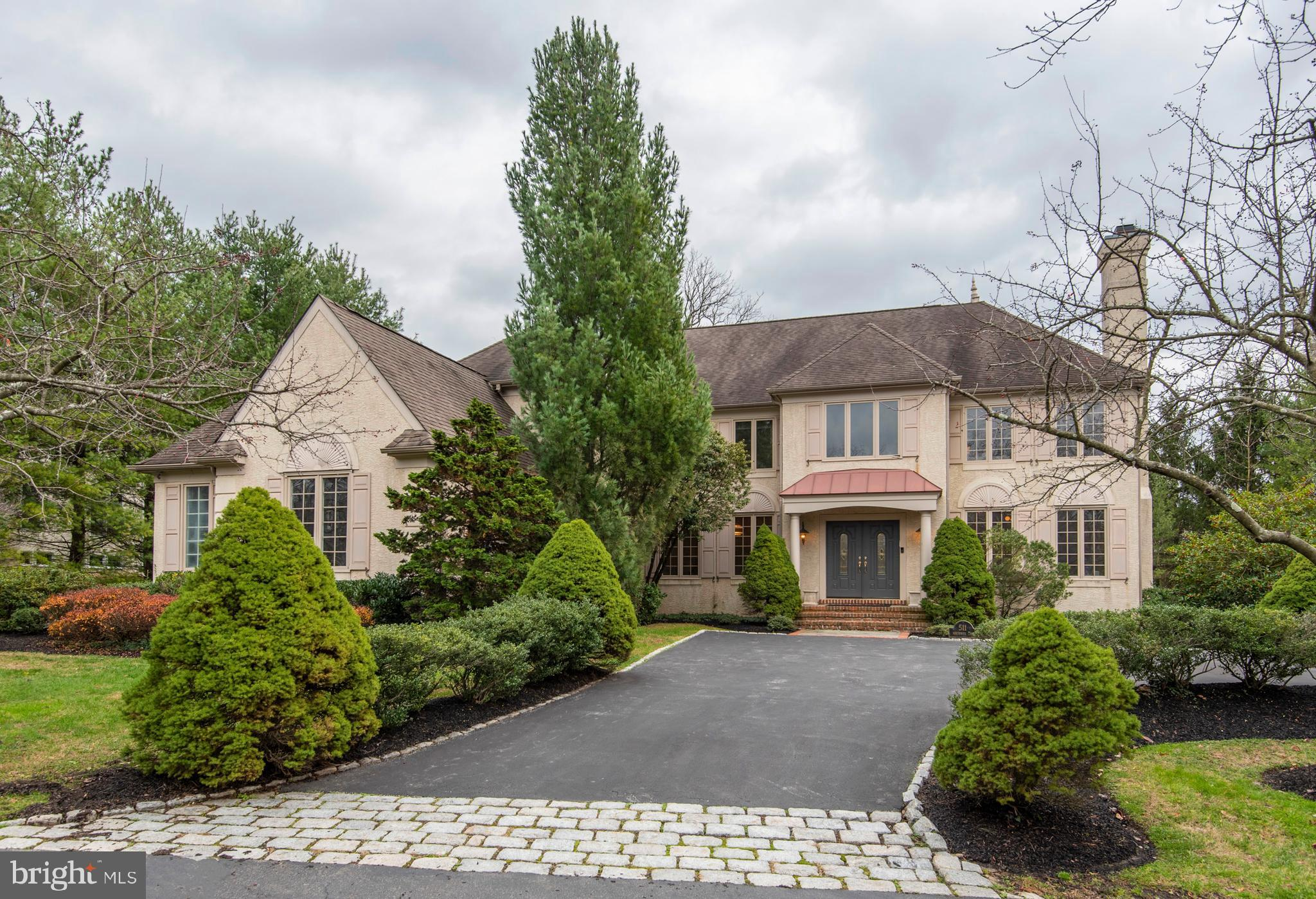 This impressive French-style Colonial is situated on a beautiful lot off of a private cul-de-sac in a quiet community in Villanova. It features an elongated driveway to the 3-car garage, and a separate formal drive with Belgium block and paver edging. You will admire the many details including the hardwood floors, architecturally appealing custom mouldings throughout, and light-filled views from every window. Enter through the double entrance door into the large center hall with curved staircase. From here you will notice the open floor plan that effortlessly flows from room to room. The main level study provides comfort and convenience for the work at home professional, and is complimented by the custom built-in bookshelves. The living room with marble fireplace and the spacious dining room give off a wonderful ambiance for entertaining. The gourmet kitchen has an abundance of prep and storage space with custom cabinetry, granite countertops, tile backsplash, sub-zero refrigerator, 6-burner Wolf stove, double wall ovens, peninsula with bar sink and bar seating, cathedral ceiling with skylight, recessed lighting, and an adjacent, light-filled breakfast room with Atrium door that walks out to a paver patio. The breakfast room is open to the fireside family room with vaulted ceiling and Palladium windows that overlook the private yard. A large mud room/laundry room, and both a formal and informal powder room complete this level. Upstairs you will find an exceptional main bedroom suite featuring a sitting room, his-and-her walk-in closets, separate vanity area, and a luxurious private bath. The main bath is complete with double bowl vanity, oval shaped jetted tub, over sized marble shower, and a water closet. The Prince/Princess Suite  features a private bath and walk-in closet, and the two additional large bedrooms share a bath. In the lower level you will find lots of additional living space including a great room giving you endless possibilities for a theater, game 