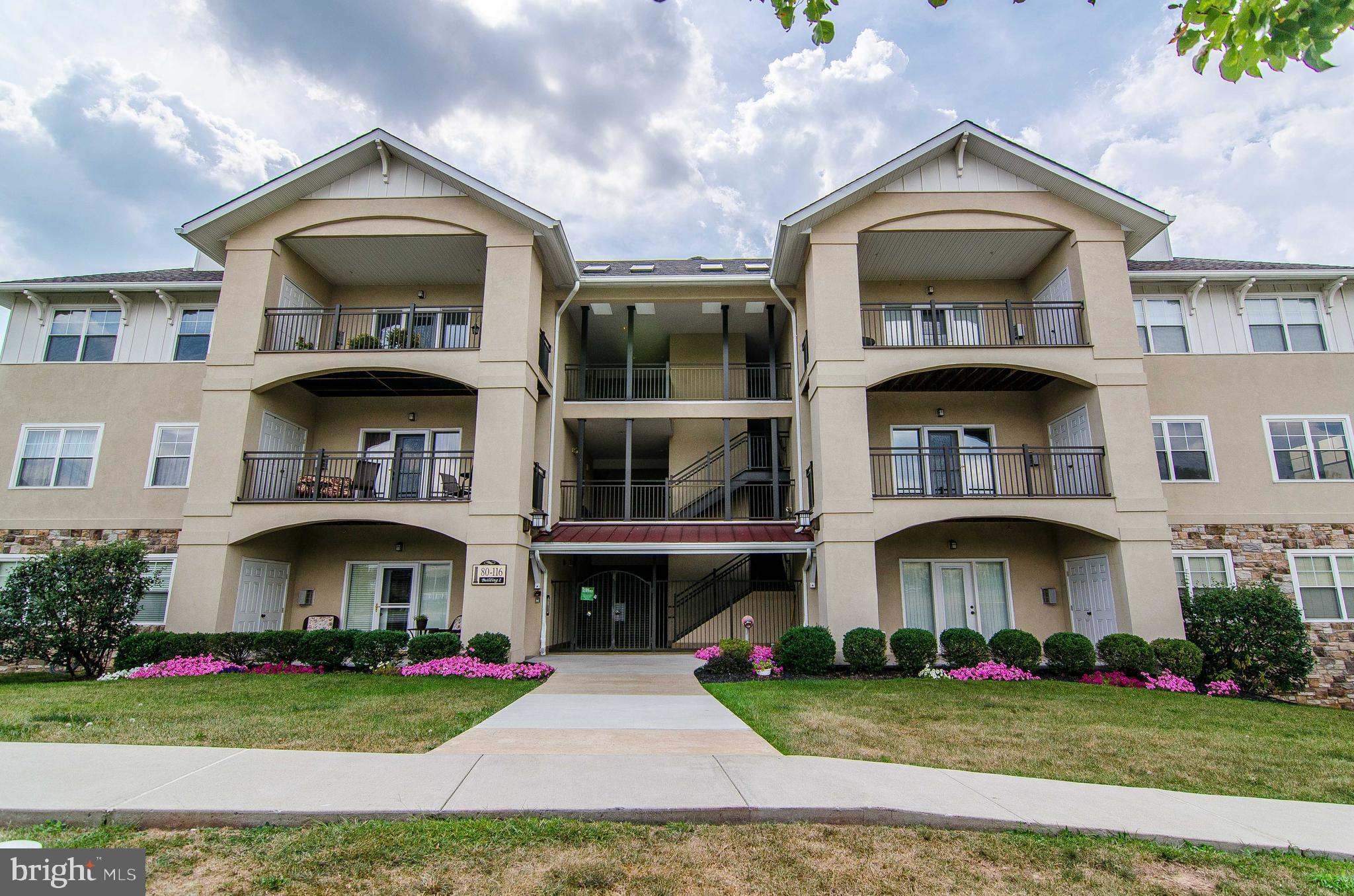 """First floor condo with updates galore! Located in the rolling hills of Chester County, Bucktown Crossing 55+ Condominiums have all you need to begin care-free living! Luxurious amenities include a secure underground parking area, full access elevator, on site storage, and secure gated entry to each building. This resale """"Bellewood"""" model, the largest unit in the community, has been recently upgraded and boasts an open concept floor plan perfect for entertaining - hardwood foyer, 9' ceilings, large kitchen with granite countertops, tile backsplash, breakfast bar, and large pantry closet, dining area with crown molding, and living room with corner gas fireplace and walk-out to the private rear balcony. The master bedroom has a large walk-in closet, wall-to-wall windows offering lots of natural light, and an en-suite bath with dual  vanity and walk-in quartz-surround shower with seamless glass door. Finishing out the unit is a spacious guest room with a double closet, full hall bath with tub, in-unit washer/dryer closet, and plenty of storage space. There is a beautifully furnished clubhouse with a card room, full kitchen, social room with fireplace, and fitness room, as well as an outdoor recreation area, including a heated pool, tennis courts, and picnic pavilion w/ grills.  The exterior is getting a facelift and this building is currently getting all new windows and siding! Just minutes from 422 and the PA Turnpike, and a 30 minute ride to West Chester and King of Prussia, you will enjoy the beautiful countryside in the most convenient way!"""