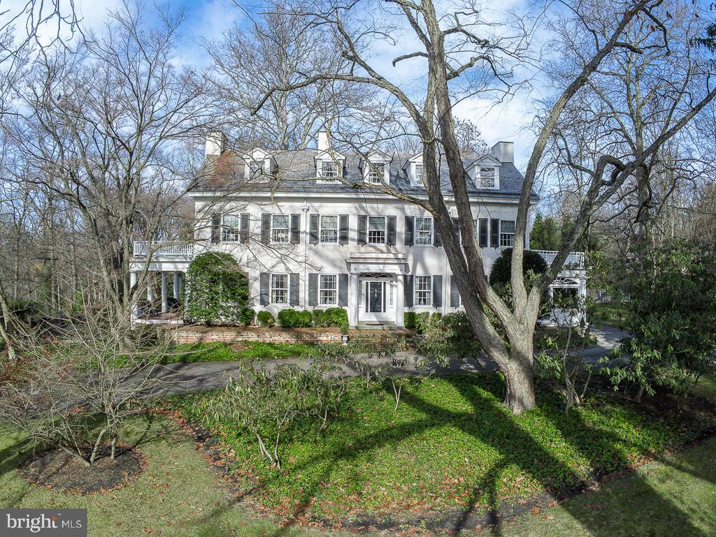 Don't miss your chance to experience a piece of history! This property includes an elegant, 3-story home and 2 bedroom guest suite/artist studio over the  detached garage. This elegant Manor home, with 7 Fireplaces, was originally built by Samuel Williamson in 1885, originally part of a 400+ acre estate.  A long sweeping drive leads up to the formal entrance, featuring the home's signature arched transom window, and majestic front door. This home was made for family enjoyment or a hosting a grand event whether it is a family wedding or a charitable occasion. The entry hall expands graciously from the formal living room with fireplace and covered terrace to the gorgeous dining room with adjoining sun-filled  solarium and old-fashioned butler's pantry. The center of the home is the den which can be opened to add flow to the party or closed off for a quiet space to snuggle on the couch in front of the fire. The updated eat-in kitchen is just a few steps away through the back hall and includes professional grade stainless steel appliances, kitchen island with seating, granite counters and built-in cooktop. The kitchen spans the back of the house and has access to adjacent laundry room and covered back porch. The architectural style of the home is evident in the staircases, whether it is the grand front staircase winding up to the 3rd floor emphasizing the elegance of the front of the home or the rear staircase connecting you from the top floor all the way to the basement, embodying the charm and coziness of the rear extension. There 6+ Bedrooms and 7 fireplaces in this home! At the top of the main staircase is the 2nd floor landing. The expansive primary bedroom has a fireplace, full bath with dressing room, and French doors opening onto a private balcony. There is also an adjoining full bath which could be shared by bedroom #2. The 3rd bedroom, with its own fireplace, overlooks the side yard and stone patio with fishpond and fountain. Office #1, also with its own firep