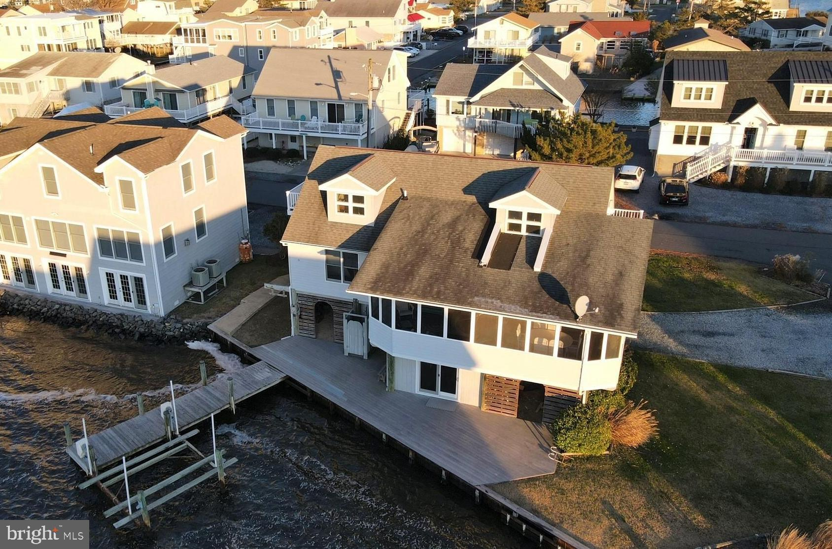 Incredible bay views from this direct waterfront home situated on 2 bulkheaded lots (502 and 504 Glenn Ave) and located within walking distance to the beach! This coastal home features an open floorplan with the living room flowing into the combined kitchen/dining area and opening to a large waterfront screened porch. Offering stunning bay views from almost every room in the home and a private boat ramp plus powered boat lift and dock that offers space for multiple watercrafts, this is a water lovers dream. Enjoy breathtaking sunsets over the bay from the screened porch, waterfront deck, or balcony. Located on the corner of a quiet non-thru street with easy access to the beautiful wide lifeguarded beach or the many restaurants, boutique shopping, mini golf and water slides that make Fenwick Island special.
