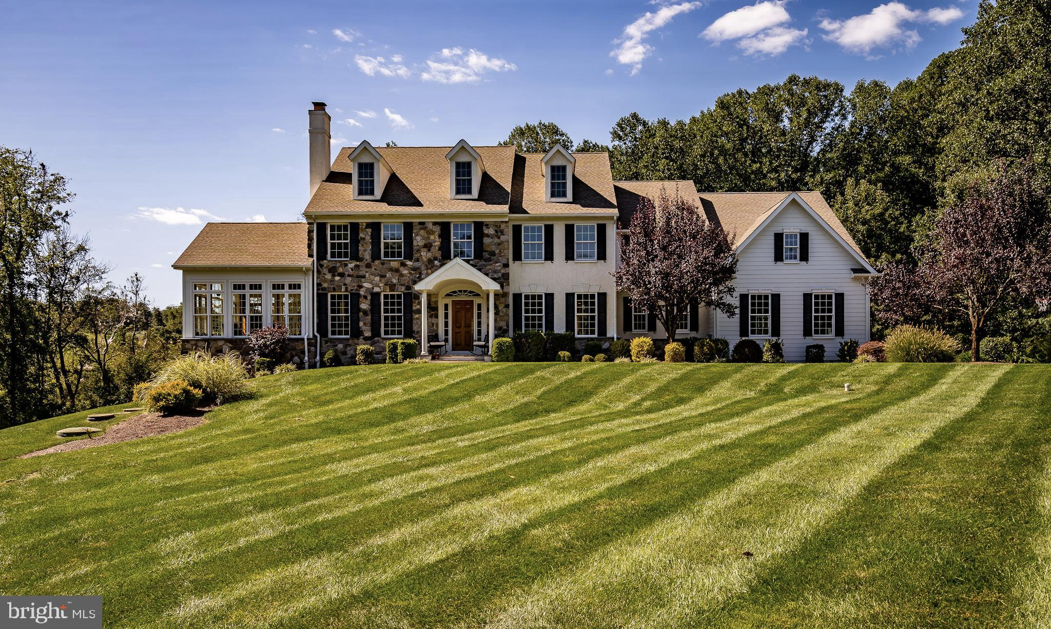 Set in the exclusive Coltsfoot community and in the award-winning Downingtown Area School District, sits this impressive 5 bedroom, 4.2 bath customized home that is loaded with tasteful upgrades. This stately home was constructed by Bancroft Construction whose name is synonymous with high quality and attention to detail. This was their sample home so nothing was spared in its construction! The main level has a wonderful floor plan that is perfect for those who like to entertain. From the flagstone front porch and solid wooden front door, you are greeted upon entry with a two-story Foyer, beautiful  staircase, and surrounded with exquisite moldings. The gracious openings from the Foyer leading into the adjoining Living Room and Dining Room showcase extensive cabinet work which is the hallmark of this builder's exceptional craftsmanship. The Living Room connects to the dramatic Conservatory with its cathedral ceiling and walls of windows. A short hallway from the Foyer leads to a Study with a wall of bookshelves and large window. Also found here is a Formal Powder Room and a spacious Coat Closet. Adjacent to the Dining Room is a handy Wet Bar with lots of storage space, an under counter refrigerator, and a granite counter. The Kitchen is a chef's delight - perfect for creating anything from an intimate dinner for two to a grand feast for the extended family. The Kitchen boasts a Sub Zero refrigerator, a Bosch dishwasher, duel Bosch wall ovens, and a five burner Bosch cooktop. You will appreciate the kitchen's abundance of storage behind creamy white cabinetry with numerous slide-out drawers and shelves. A stunning tile back splash and granite counters add beauty and function to this lovely kitchen. Found here is a rear staircase to the upper level as well as the access to the lower level. The Morning/Breakfast Room opens to the rear Deck and is surrounded by glass that floods the area with natural light. The adjoining Family Room could have blessed an interior design 
