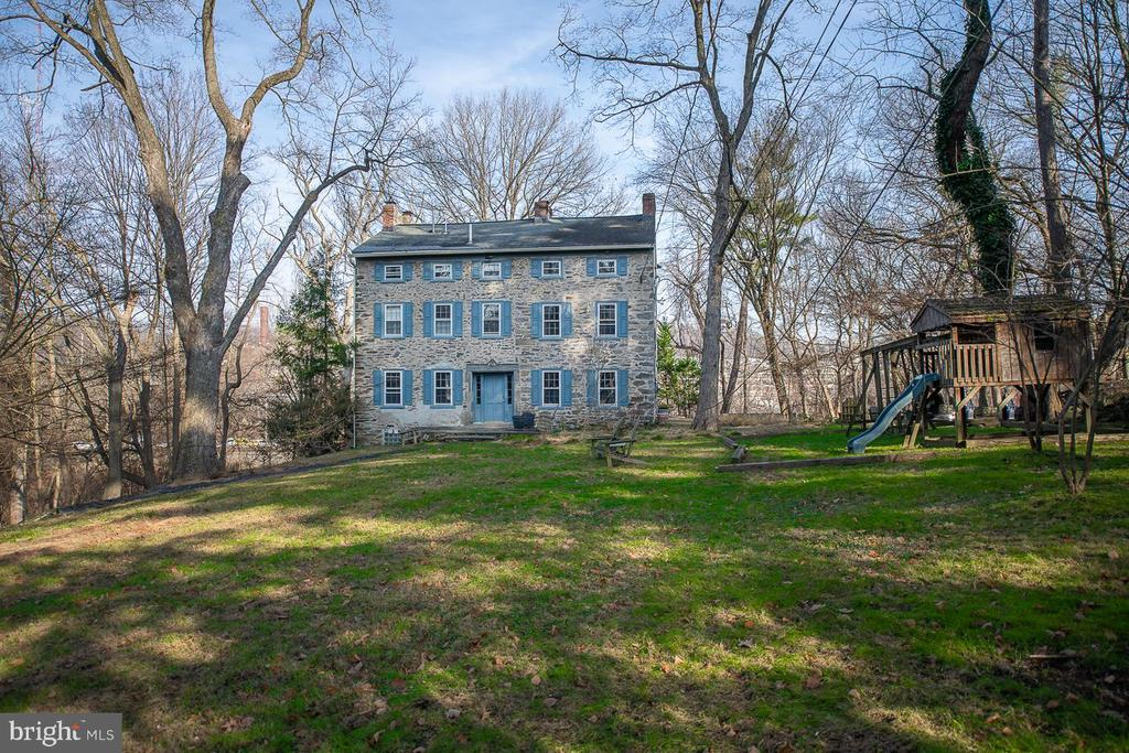 It will be a privilege to own and honor this class 1 historic home built in 1787 on a large secluded yard set far off the road.  Leedom House has solid unusually  thick stone walls that create an interior of peace and  quiet.   Entering the front hall the well preserved, stunning  original woodwork including curved bannister running up to 3rd floor, deep window sills, fireplace and random width flooring jumps out. The large, charming, living room with fireplace is filled with light on 3 sides. Across the front hall is the kitchen with an enormous tiled counter facing the Viking range and a nice, well lit eat-in space. The kitchen door leads out to convenient parking. The kitchen opens into a large playroom/office/exercise room with separate powder room on backside of house.   Second floor has a very large bedroom on one side with excellent storage space and  fireplace  and there is a smaller bedroom with enclosed full bath on other side of hallway. In hall is another full bathroom.   The third floor has a very large double height vaulted ceiling bedroom on one side, and a smaller bedroom/office/library on other, again  with enclosed full bath and as per floor below another  full bath in hall. The creative possibilities for using this combination of spaces are endless.   On the bottom floor of this 4 story home there is an apartment which has 2 doors to the driveway outside at grade (note- you also can  enter upstairs to  both kitchen and front hall at ground as well because Leedom  house is on a slight grade). The apartment is accessed on interior downstairs off kitchen and has its own kitchen, living room, bedroom, good storage spaces, washer/dryer and full bath. Note the well preserved original cook-in colonial wall oven- a delightful artifact harkening to when this home was one of just a few for miles around!     The yard is nicely landscaped, has a large expanse of grass and has a wooded section including some cool old stone walls remnant of colonial out buildin