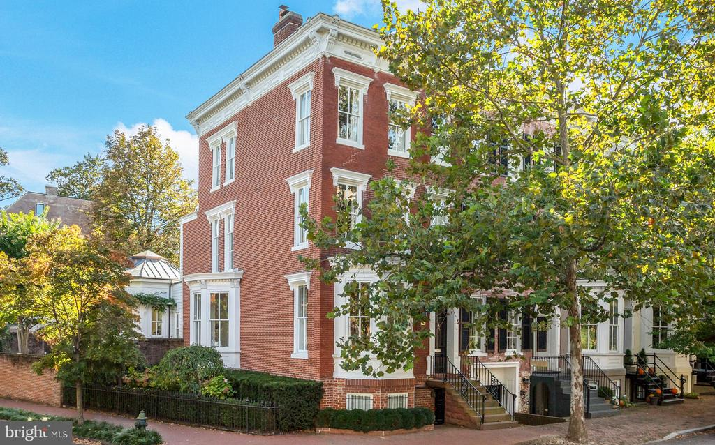 This handsome semi-detached brick residence is sited on a prominent corner lot in the heart of Georgetown.  The Italianate-style house was built in the late 19th century and was recently renovated by Barnes Vanze Architects and Falcon Construction. The house is illuminated by abundant natural light through large windows on three sides, which is further magnified by the dramatic high ceilings. It is walking distance to restaurants, shops and boutiques, neighborhood parks, and the Georgetown Waterfront. The charming front vestibule leads to the bay-front living room with a fireplace and built-ins. There is an additional sitting room/library, which is complemented by an attractive bay window. The adjoining dining room is accessed through double doors. The gourmet kitchen has beautiful marble countertops, pantry storage, a large center island with breakfast bar, and high-end appliances including Wolf and Subzero. The kitchen overlooks the beautifully landscaped back garden through three large windows. The neighboring family room with paneling is sun-filled, with windows on all sides, additional transoms, and a large central skylight. It provides convenient access through glass-paned French doors to the rear deck and garden. There is a lovely powder room with a marble sink found on this level. The luxurious owner's suite encompasses the entire second level. Nearly floor to ceiling windows provide the bedroom with spectacular eastern sunlight. There is an adjoining office or sitting room, two well-appointed marble en-suite bathrooms, and dual walk-in closets with built-ins. The third level offers two additional bedrooms and a full bathroom. The lower level of the residence has a recreation room, fourth bedroom, full bathroom, and a laundry room. The generously-sized rear garden is fully fenced and mature trees provide additional privacy. The residence also offers one-car surface parking.