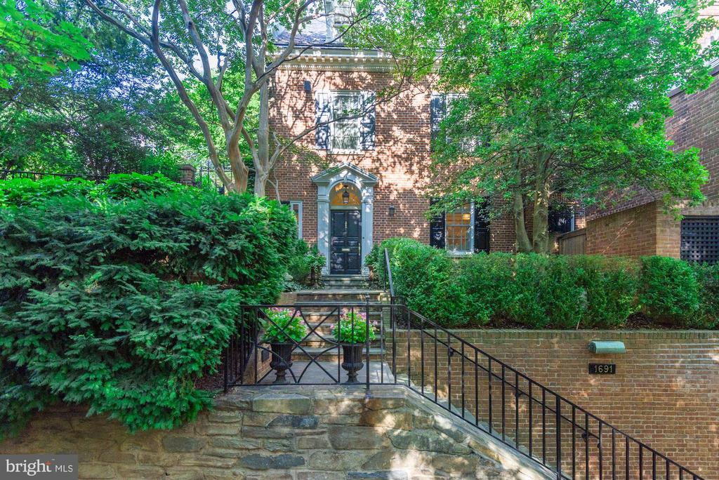 This distinguished Federal-style residence is desirably located among many prominent houses in historic Georgetown. Set back from the street, the house has a commanding façade of traditional brick, which is enhanced with detailed custom millwork.  The house has been called home by various well-known Washingtonians, including U.S. Senator Charles H. Percy. The house is ideal for entertaining and has hosted prominent DC political figures, including United States senators, congressmen, and members of the diplomatic corps, for extravagant parties and social gatherings. The main house features generously proportioned rooms and a seamless flow from indoors to outdoors. A large private terrace, separate renovated pool house, elevator, and heated pool are some of the remarkable features of this exceptional residence. The charming arched-front vestibule leads to the reception foyer, complemented by marble floors, elegant moldings, and splendid architectural details. The sophisticated living room is south-east facing, with an original fireplace and handsome bay window overlooking the lush rear garden. The fully renovated gourmet kitchen offers marble countertops, high-end appliances, and abundant cabinet space. The kitchen can be closed off with pocket doors and perfectly adjoins the exquisite dining room, enhanced with beautiful inlay floors. It opens onto the neighboring family room with attractive cherry wood finishes. The family room accesses the rear garden through floor-to-ceiling glass paneled doors, further illuminating the room with an abundance of natural light. There is the added convenience of a powder room on this level.  An elegant curved stairwell leads to the gracious second level.  The well-appointed owner's suite captures southeastern sunlight and has two walk-in closets, built-ins, and a private sitting room. Luxury is exemplified through the spa-inspired marble bathroom with dual vanities, a frameless glass shower, and separate soaking tub. There is an additional bedroom on this level with an en-suite bathroom, two closets, and a private balcony. The secondary laundry room is also conveniently located on this floor. The third level has two more bedrooms, one of which has its own adjoining sitting room or office with a beautiful wall of windows and a walk-out balcony, providing sweeping views of Georgetown. There are also two full bathrooms on this level. The expansive lower level features a separate foyer entrance with paneled walls which leads to a mudroom with a secondary refrigerator and ample storage space. There is a a fifth bedroom, full bathroom, and a laundry room, making this an ideal space for a staff suite. There is a remarkable media/recreation room and access to the garage and pool house from the lower level. The fully renovated pool house has vaulted ceilings, beautiful wall paneling, a fireplace, full bathroom, and kitchenette. There is convenient access to the rear terrace and pool through large glass-paned French doors, which also provide wonderful sunlight to the spacious interior. A one-car garage provides the house with an exceptional amount of additional storage space.  The beautiful grounds are fully immersed with lush greenery and mature trees. There are multiple gardens, all of which have been professionally landscaped and capture light from the south and east. The private rear terrace offers a heated pool and multiple spaces for outdoor dining. The residence is walking distance to the Georgetown Waterfront, parks, and many fine restaurants and boutiques.