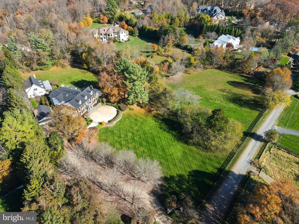 Paradise found with this tranquil beauty! A unique opportunity to have over 5 extraordinary acres with mature trees and sweeping lawn on the border of McLean and Great Falls.  As you enter the gates you are greeted by a tree-lined, cobblestone path leading to the Main House that is a quintessential balance of comfort and elegance with custom high-end finishes and a charming Guest House.  Once you are welcomed through the front door you will feel right at home with spacious formal rooms perfect for entertaining, Custom-designed Kitchen with top-of-the-line appliances, oversized Marble Island, Coffee Bar, Pantry with extra Refrigerator and Breakfast area with floor to ceiling windows that opens to the screened-in Porch with Fireplace. The Upper Level has a fabulous Owner's Suite that includes a luxurious Bedroom with Fireplace, sumptuous Spa Bath with heated floors, walk-in Closets, Breakfast Bar, Office and Balcony with spiral staircase. There are four additional Bedrooms and a fantastic Laundry Room on the Upper Level. The walk-out Lower Level includes a wonderful Recreation Room, Home Theater, Guest Room/Gym with Full Bath, Wine Room and Bar that opens to a covered Terrace and lots of storage inside and out. The Guest House does not disappoint with superior high-end design features that include a beamed vaulted ceiling on the Main Level, 2-story Stone Fireplace, Kitchen, Powder Room, Laundry area. The Second Level includes Bedroom, Loft and Full Bath. There is 3-Car Garage, spectacular gardens and the breathtaking grounds are fully fenced with Gated Entrance! Total square footage oh home is 11,188 that includes the Guest House!