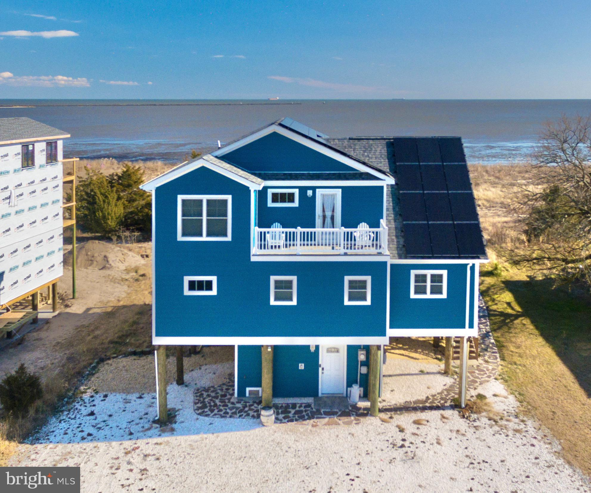 Waterfront on Slaughter Beach -- virtually new - just 2 year young custom home located on a cul-de-sac at the end of Beach Plum Drive.  This custom home delights at every turn -- pull up to beautiful Ocean Blue Hardie-Plank siding and with solar panels to keep those energy bills low.  2700 sq ft home with 4 bedrooms, 2.5 baths.  Beautiful open floorplan -- living area opens to dining and kitchen as well as tiled 4 season room and decks with stunning views of the Delaware Bay and its amazing sunrises.  Kitchen features granite countertops, stainless steel farm sink, Wolf cabinetry, GE Black Slate, finger-print resistant kitchen appliances, contemporary subway tile backsplash, convection oven and French door refrigerator.  Main level primary bedroom with bay views with gorgeous bath -- double sink, granite countertop, soaking tub and beautiful tiled shower with corner seat. Multiple Duradek decks for great views and low maintenance. Main level laundry with LG Graphite side by side washer/dryer.   Custom pathway to the bay with shed under home to store those beach toys.