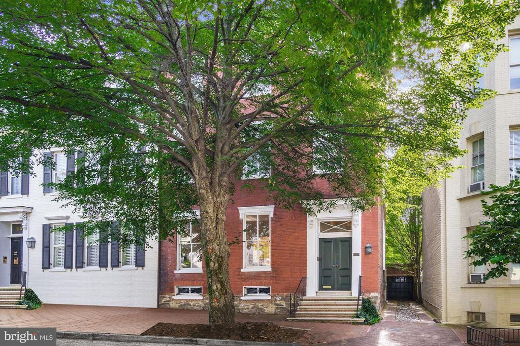 Handsome 18th century brick Federal with magnificent proportions in the East Village of Georgetown.  It has a two-car garage plus driveway, deep garden, high ceilings, ample bedrooms, spacious entertaining rooms, light-filled family room off  large kitchen, lots of storage space, double living room, upstairs library, primary bedroom with sitting room and two primary baths, home office, original flooring and details, back staircase, and tons of light in every room.