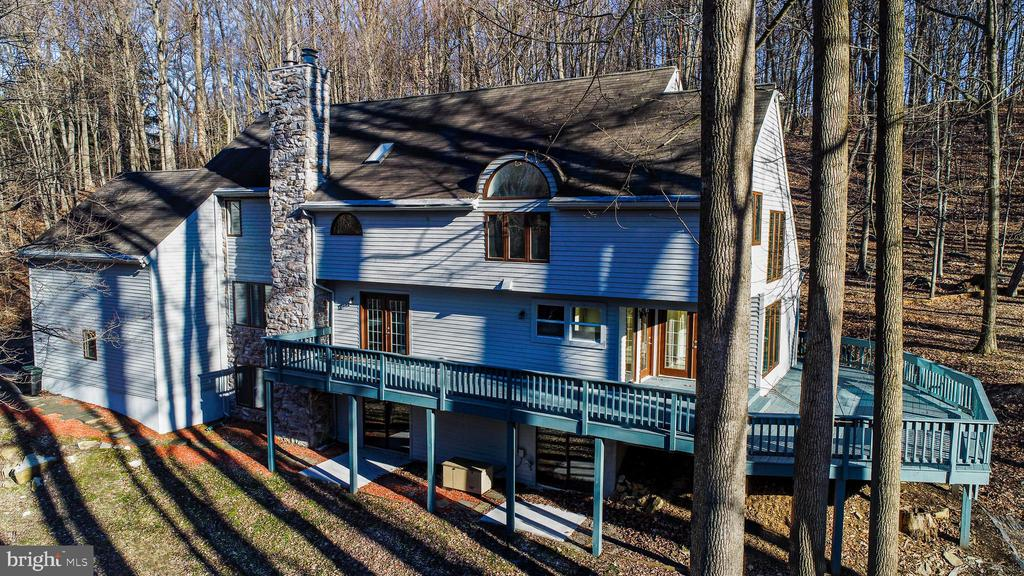 Quiet contemporary  home in a wooded setting. Generous open floor-plan w/ lots of windows boasts tons of sunlight and out door living. Living rm/dining rm combo w/gas log FP &  hardwood flooring. Bright great rm w/gas log FP, hardwood fl & wall of windows.Large kitchen w/breakfast bar & sunny eating area lead to custom wrap around deck reaching the entire length of home. The kitchen is a chefs dream, industrial gas stove/oven surrounded by granite counter top.  The Main bedroom is oversized with 2 walk in closets and spa like bathroom,  2 additional BRs, full BA, Laundry closet and bonus room. 1st FL features a study/optional 4th BR w/full BA. 2 car garage w/ loft above is finished for hobby/storage area. Basement is finished, features walk out, wood FP, work space & storage galore.Whole house generator