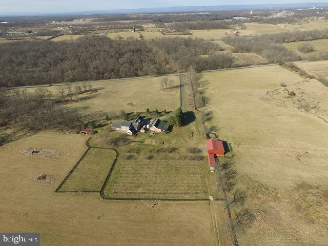Incredible opportunity  that rarely comes up! 65+ acres of beautiful crop land or bring on the cattle and /or horses!  Level, mostly 4 board fenced, this land also offers mixed use for gardeners.  Twenty two mixed fruit trees and a 96 vine vineyard now on site. Make your own wine and jams! The all brick home offers  4 bedrooms, plus has a full unfinished basement with a full bath already completed, and a wine cellar.  The two car attached garage has a finished in-law suite above, PLUS there is a rough-in for additional living over the detached garage.  Feel the flow and the ease of entertaining when you walk through the front door into the large living room (now housing two grand pianos!)  The formal dining room is right off the gourmet kitchen with all of these rooms  facing beautiful mountain views in the rear.  The kitchen's highlight is the 6 burner Viking stove.  The kitchen leads right into the oversized family room with high ceilings and wood burning fireplace.  A large screened porch  with brick flooring invites you to enjoy the outside and the views.  With two bedrooms and a full bath up , the large master suite on the first floor and a bedroom with bath above the garage,  this is the perfect house for guest stays. Floor plan in docs.  For the  potential farmer, we have 6 outbuildings including run-ins, small barn and lots of storage. The property is offered with some trailers, tractor w/mower, and a  Kuboda  ATV among other items. Elk Run stream meanders through the north portion of the farm.   Perfect for horses with Charles Town Racetrack 15 minutes from the farm.  No herbicides, pesticides, fungicides and insecticides since  2015. Approximately 6 wooded acres. Located about 55 minutes from Dulles Airport;  approx 7 minutes from the commuter train station in Duffields;  and with easy access to Shepherdstown , Charles Town and Leesburg. Surrounded by farms on three sides and a church and woods on the southside.
