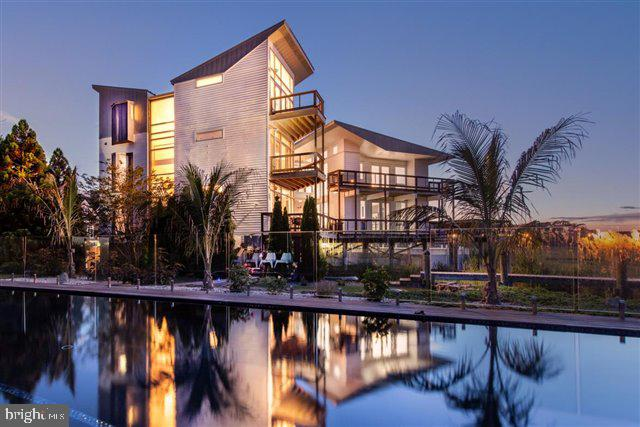 Welcome to this extraordinary contemporary meticulously designed 6050 sq. ft. home.  This incredible residence is situated on an acre of waterfront located on the bay, in the White Marlin Capital of the World! This home was updated in 2020 with over $150,000 upgrades, including: all new Elan Smart Home Technology System and Lutron Integrated lighting. When you pull into the circular driveway your senses heighten and you realize what an amazing art form this home is.  From the craftsmanship, constructed with the finest materials curated from across the world. The expansive use of glass, steel, concrete, and wood creates a one of a kind luxurious  modern architectural masterpiece. The minute you walk through the front door you feel how the house embraces with its seamless design that connects to the beauty of the bay and all it has to offer. An exceptional abundance of glass elements allows for the flow of natural light throughout the home.  Features a state of the art Boffi kitchen and master spa bathroom made in Milan.  The master suite is located on the 3rd floor is a serene setting with a private balcony encasing the bay. Complete with comfort and style with a spa bath and dressing lounge.  A skywalk connection enclosed with glass and marble tile takes you to the second architectural masterpiece living space complete with fitness center, lounge area, guest suites with soaring ceilings, and multiple decks.  The second master suite is airy with a loft style complete with a 600 lb. Corian tub with Terrazzo tile flooring and custom rain shower.  Enjoy summer days by the black bottom saltwater pool, private pier, hot tub, fire pit, fitness center, and custom waterfall with koi pond.  If you are a car enthusiast the heated and air conditioned garage with glass panels to showcase your luxury car.  End the day with a breathtaking sunset.  This is luxury living for the most sophisticated buyer, close to world class marinas, airports, dining and shopping.  Seller will accept Bitcoin (as well as cash and mortgage )  as a form of payment to purchase this stunningly beautiful property.