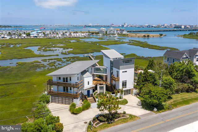 Welcome to this extraordinary contemporary meticulously designed 6050 sq. ft. home.  This incredible residence is situated on an acre of waterfront located on the bay, in the White Marlin Capital of the World! This home was updated in 2020 with over $150,000 upgrades, including: all new Elan Smart Home Technology System and Lutron Integrated lighting. When you pull into the circular driveway your senses heighten and you realize what an amazing art form this home is.  From the craftsmanship, constructed with the finest materials curated from across the world. The expansive use of glass, steel, concrete, and wood creates a one of a kind luxurious  modern architectural masterpiece. The minute you walk through the front door you feel how the house embraces with its seamless design that connects to the beauty of the bay and all it has to offer. An exceptional abundance of glass elements allows for the flow of natural light throughout the home.  Features a state of the art Boffi kitchen and master spa bathroom made in Milan.  The master suite is located on the 3rd floor is a serene setting with a private balcony encasing the bay. Complete with comfort and style with a spa bath and dressing lounge.  A skywalk connection enclosed with glass and marble tile takes you to the second architectural masterpiece living space complete with fitness center, lounge area, guest suites with soaring ceilings, and multiple decks.  The second master suite is airy with a loft style complete with a 600 lb. Corian tub with Terrazzo tile flooring and custom rain shower.  Enjoy summer days by the black bottom saltwater pool, private pier, hot tub, fire pit, fitness center, and custom waterfall with koi pond.  If you are a car enthusiast the heated and air conditioned garage with glass panels to showcase your luxury car.  End the day with a breathtaking sunset.  This is luxury living for the most sophisticated buyer, close to world class marinas, airports, dining and shopping.  Seller will accept Bitcoin and Ethereum (as well as cash and mortgage )  as a form of payment to purchase this stunningly beautiful property.