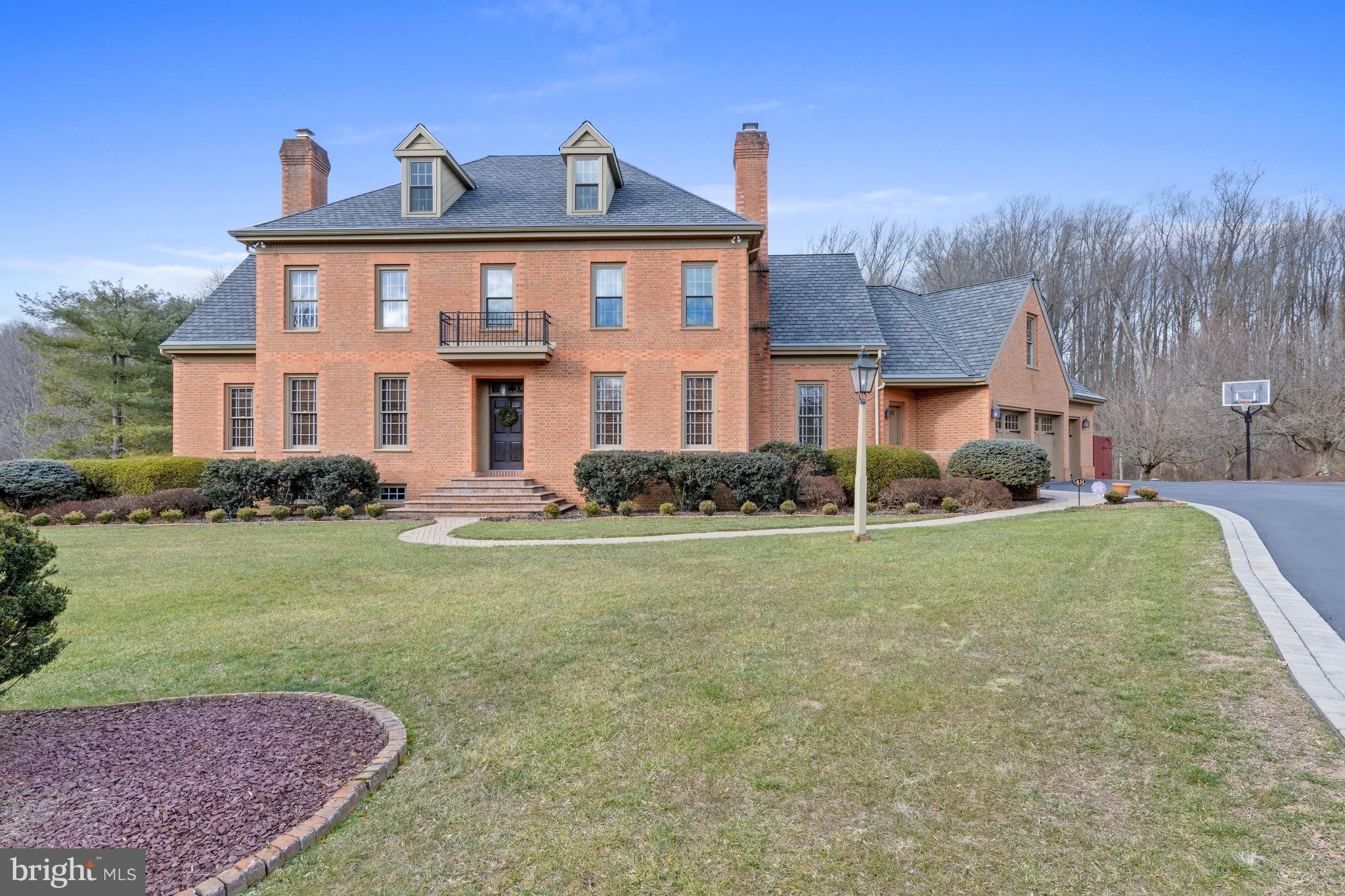 This stunning classic brick colonial home is set on a private lot cul-de-sac and was modeled after the Joseph Howard Hennage House of Williamsburg, VA. The exterior is made of genuine Cushwa Brick and was constructed using the Flemish bond fashion, the hallmark of Classical Architecture first appearing in medieval Europe's Frauenkirche of Munich in 1468 with the earliest surviving American example on St. Lukes Church, Isle of Wight County, VA. Enter into the impressive foyer with spiral staircase fashioned after the spiral stairway of the Rotunda of the University of Virginia. Immediately notice the gleaming hardwood floors that run throughout most of the home as well as the custom millwork by Van Heyneker Fine Woodwoking and the Larkin Co. The foyer is flanked by the formal living and dining rooms both with wood fireplaces. Continue straight to the custom chef's kitchen with custom inlay 2-tone cabinetry, island with seating, top-of-the-line appliances and hidden pantry. Connected to the kitchen is a breakfast room with walls of windows overlooking the private yard. The 2-story family room sits off of the kitchen with built-in media center and gas fireplace. The private study is tucked at the end of the hall with built-in shelving. A sun room sits off of the kitchen and offers an abundance of natural light. Both formal and informal powder rooms, laundry room and access to the 3-car garage with doors by Designer Doors, Inc complete the main level. Up the main staircase find the owner's suite with his and hers walk-in closets and beautiful Waterbury bathroom. Two additional bedrooms share an updated guest bath and a large in-law suite with 5 piece bathroom finishes the second level. Continue to the unfinished 3rd level which offers endless possibilities for customization. The finished walk-out lower level is currently set up for an in-home gym and has a full bath. Enter the sprawling brick patio through numerous entrances from the main level and relax by the heated p