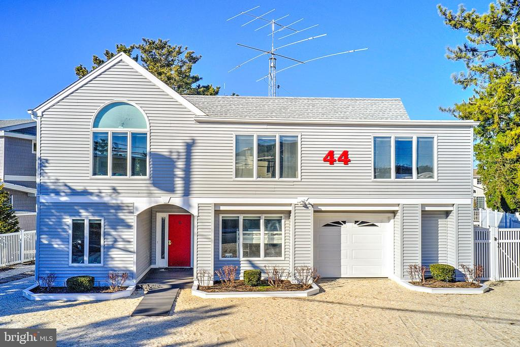 Showings to start  Friday,  March 5th.  Located in Loveladies Harbor on the lagoon with 80 ft. on the water, this multi-level home encompassing nearly 2600 sq. ft. of living space highlights beach house living at its best both inside and out.  This much loved, well maintained, and tastefully appointed home was totally renovated in 2019 and boasts 5 bedrooms, 3 baths, and endless spots to congregate.  The oversized living room, dining room, and kitchen take up an entire floor to itself, making gathering and entertaining a pleasure. A large master ensuite, two sizable guest bedrooms, a full hall bath, and a functional laundry room round out the top floor space.  The first floor boasts two bedrooms, an oversized one-car garage with extra storage space for bikes, boards, and beach paraphernalia.  The outdoor space in this home is the talk of the neighborhood with a 16 X 36 ft. pool and free-standing hot tub, along with endless gathering spaces for outdoor dining, lounging, and game playing.  The new vinyl bulkhead and dock with a sizable raised platform is the perfect place to meet up in front of the fire pit and watch the sunset.   The fun doesn't end there as the lagoon is the ideal place to enjoy swimming, kayaking, and paddle-boarding.
