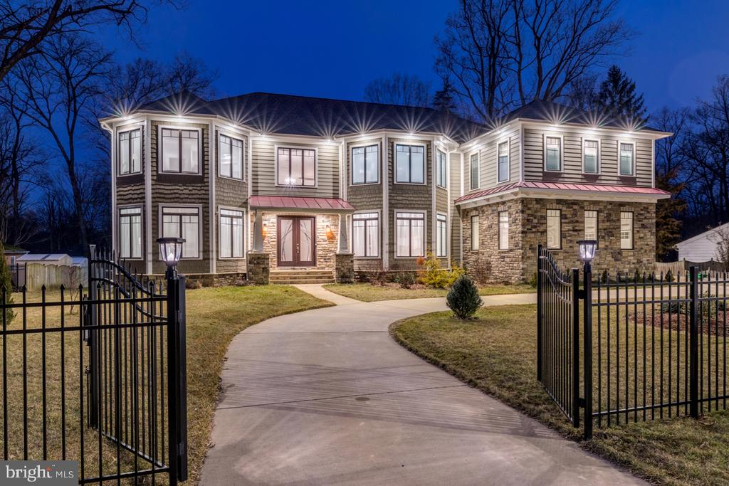 A PRIZED TREASURE: This like-new, custom-built, modern Craftsman-style home is nestled on a prime .59-acre lot, just minutes from the world-class shopping and business centers of Tysons Corner, the quaint Town of Vienna and the W&OD walking/biking trail. This impressive home features 6 spacious bedrooms across all 3 levels, including 2 primary suites with sitting rooms, large walk-in closets and spa-like baths. The property is fully fenced, with two gated entries, a circular drive and oversized 3-car garage for ease of movement and parking. Featuring expansive windows and an open floor plan, the sleek interiors are wonderful for gatherings of any size. Formal living and dining rooms are divided from the 2-story foyer by arched doorways, yet connected in back by a long hall with an exquisite barrel-rolled ceiling that opens to the great room in the rear of the home. Dramatic architectural features of the great room include a ceiling dome and crystal chandelier, Juliet-balcony-style upper foyer, and floor-to-ceiling stacked-stone fireplace between walls of windows. At the home's heart, the stunning gourmet kitchen features a large center island with bar seating, quartz countertops, high-end Jenn-Air stainless steel appliances, lighted display cabinets, and custom cabinetry that tidily holds everything from fine china to spices. The adjoining breakfast salon, perfect for informal dining,  stands open to the great room, and French doors allow access to a large, elevated deck for seamless indoor-outdoor living, dining, and entertaining. Off the kitchen, a walk-in pantry, mud-room, laundry room, side exit, 2nd staircase and garage access add conveniences. A private office with closet and bath, tucked into a rear corner of the home, could also be used as a main level bedroom. In addition to the 2 owner's suites, the upper level offers 2 additional bedrooms with baths, and the 2nd laundry room. The lower, recreation level of the home also features an open floor plan, with areas for lounging, dining, billiards and other games, fitness, and a home theater with surround-sound system, as well as a wet bar, fireplace, bedroom suite, half-bath, and walk-up exit to the expansive rear yard. Other amenities include rich hardwood flooring throughout the main and upper levels, security system, chandelier lift systems, whole house audio system, and an ELEVATOR-READY shaft that offers additional access between the 3 levels.