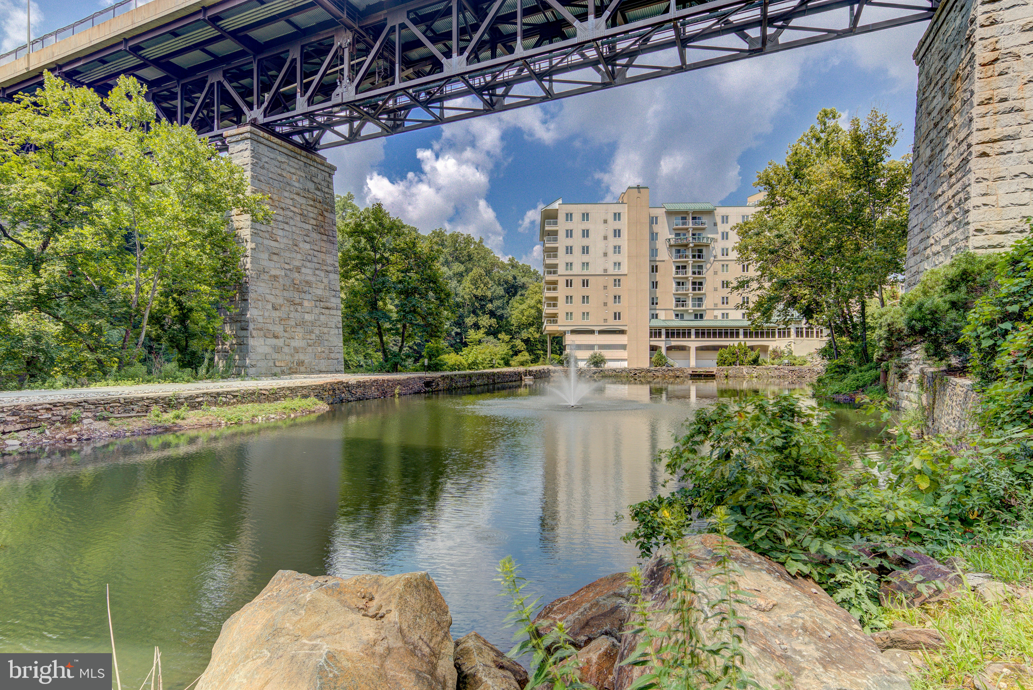 Follow the quiet and private road along the Brandywine River and enter through the security gate to The Pointe. Take the private elevator to your secluded foyer. Immediately notice the large open floorplan. This model apartment features updated fixtures, flooring, kitchen and baths. To the right of the foyer is a storage closet, which has been converted into a craft room with custom cabinets and provides an abundance of space for storage. To the left of the foyer is a guest room with newer carpet. Heading towards the main living space, pass by a full guest bathroom. The main living area boasts open sightlines strait through to the wall of windows overlooking the Brandywine. The contemporary style allows you to be as creative as you want with the design, as there are various layout options. The stunning chef's kitchen features beautiful stainless steel appliances, including a subzero fridge, plenty of cabinet storage, granite counters and large L-shaped island with seating. There is enough space to include a large dining table, sitting area and family room. Tucked down a private hall is an additional guest suite with updated bath and the primary suite with large walk-in closet with shelving system, additional closet and beautifully updated bath with soaking tub, walk-in shower and dual vanity. Enter onto the sprawling balcony through 2 sliding doors and instantly indulge in the serene views of the Brandywine River and wooded area beyond. Additional amenities include a huge community room, game room, exercise room, personal storage next to your 2 reserved car spots, pool, plus wonderful walking paths just outside your door. All of this while being just steps from Trolley Square, Downtown Wilmington and all that the area has to offer.
