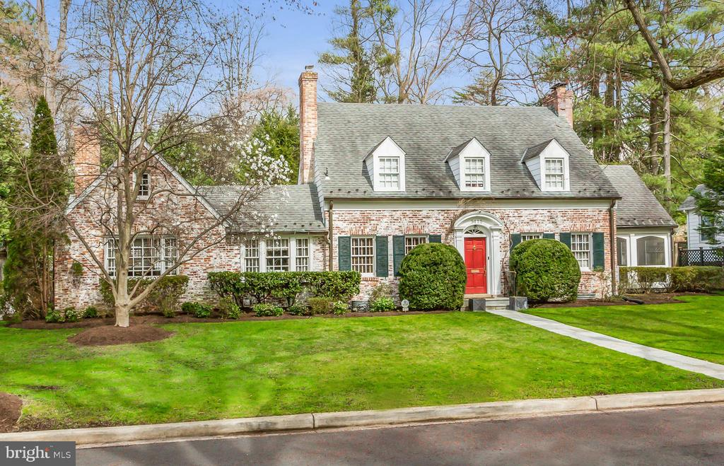 This story book white-washed brick residence is located on the most beautiful tree-lined street in Spring Valley.  The house has incredible curb appeal, featuring a charming front archway embellished with decorative molding. The spectacular residence offers a highly desirable floor plan with approximately 5,000 square feet and well-proportioned rooms. It is illuminated by an abundance of natural light from large windows throughout. The front foyer is neighbored by the sophisticated living room with a fireplace and the elegant dining room. Adjoining the living room is a lovely screen-in porch.  Both the living and dining rooms seamlessly open to the rear slate terrace through separate French doors. The gourmet kitchen opens to the spacious breakfast and great room with a fireplace and vaulted ceiling.  There is a main floor bedroom and full bathroom, as well as an office with built-ins and a fireplace. The upper levels provide three additional bedrooms and two full bathrooms, including the luxurious owner's suite. The bedroom has a spacious walk-in closet with built-ins and a spa-inspired bathroom with a steam shower. The lower level is appointed with an expansive media/recreation room, fitness room, extensive wood-paneled bar, a 1,200-bottle wine cellar, and a full bathroom with Waterworks fixtures. A limestone gravel driveway leads to the parking court and the fully customized two-car garage. The conditioned garage has been fully outfitted to include abundant overhead storage, enamel floor covering, steel cabinets/drawers with bamboo countertops, a hot and cold sink, and LED lighting. Above the garage, with separate private access, is a lovely guest or in-law suite, offering wonderful privacy and terrific sunlight. It opens to a private lawn and rose garden. The suite features a kitchen and full bathroom with Waterworks fixtures. The exceptional grounds of the .35-acre lot are meticulously maintained and showcase professional landscaping, extensive fieldstone walls, beautiful English gardens, a Koi pond, marvelous rose garden, and a flat yard.