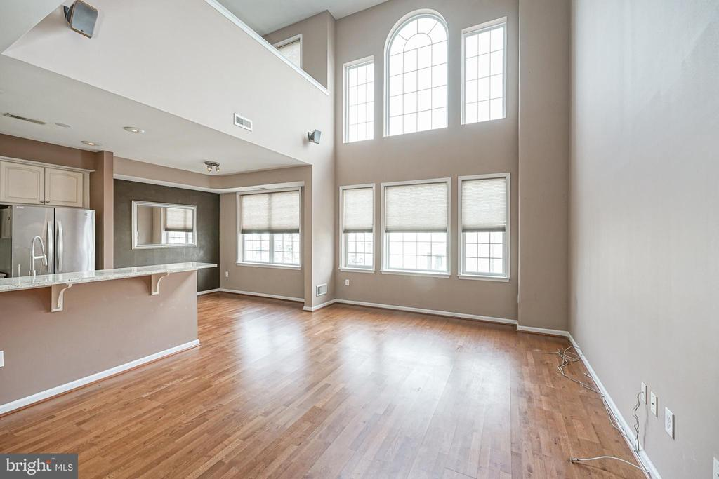 "Join this wonderful community at the Villas @ Packer Park!  This BEAUTIFUL, contemporary, end of row home is a blank slate ready for you to create your dream home.  Gorgeous Hardwood floors and soaring ceilings complement the dramatic Cathedral Windows.  The classic Kitchen is crisp and clean with white cabinets, Stainless Steel appliances, Granite countertops with counter seating, and a formal Dining area.  The Powder Room is located on this main level.  On the upper level, the open Loft area has classic ""mid-century modern"" built-in cabinets adding extra storage space along with a touch of nostalgic charm.  This Loft area can easily be converted into a 3rd Bedroom if desired.  The Master Suite has a Walk-in Closet and an en-suite Bathroom with double sinks, tub, and standing shower!  The Laundry Room is wisely located on this upper level along with the roomy 2nd Bedroom.  Spoil yourself with the attached Garage and enter directly from the Garage to your unit.  Some things to keep in mind ==> 1) This is legally a ""NO DOG OF ANY SIZE"" community, and 2) No ""Commercial Tag"" vehicles are permitted on site."