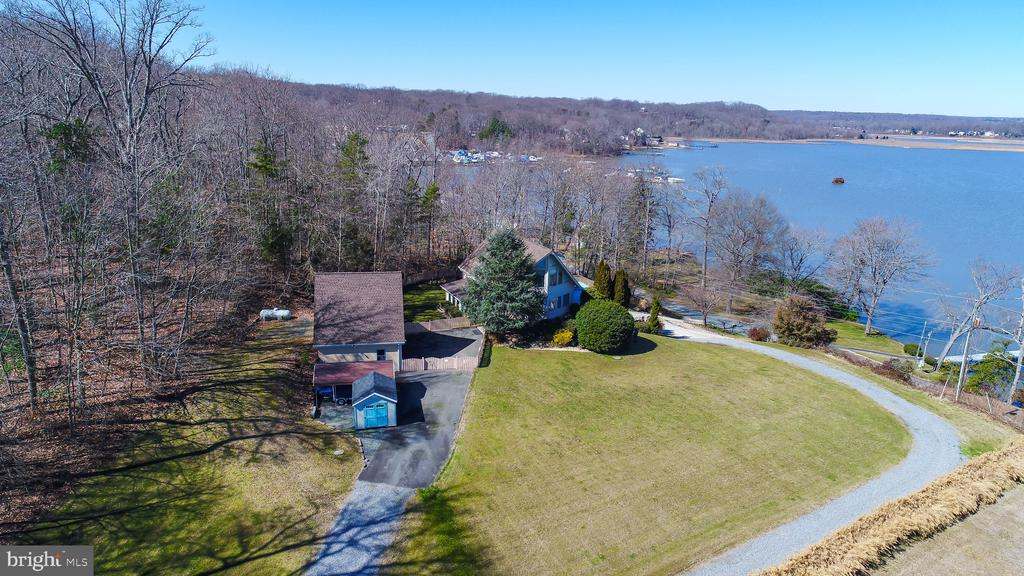 Panoramic water views and an estate like no other await at 186 Willow Landing Road! This one-of-a-kind, completely customized home is primed for entertainment opportunities galore and tranquil waterside living. Plus, the outbuildings and additional structures on-property will leave you speechless. The home was originally built in 1987 and boasts 3,840 total square feet. Public record states it is a one-bedroom, but there is plenty of open space to potentially reconfigure and make this beauty that much more of your own. The Owners use two more of the rooms as bedrooms not to code. Just like its water views, the opportunities are endless! Approaching the home - which is tucked off a quiet bend of Willow Landing Road - you'll see this is a tight-knit and secluded community. Upon arrival to the 3-acre estate, take in the dynamic terrain and its recent landscaping enhancements, spanning its large grassy areas, gardens and woods. Let's head inside, shall we? Through its front door, a sea of gleaming hardwood floors and natural light await. To say this home has an open floor plan would be an understatement. Its main level is anchored by a lovely living room with windows that showcase 270-degree views of Aquia Creek from virtually any vantage point. There is a cozy stove to keep you warm on those frigid winter evenings. Also on the main level is an open kitchen complete with stainless steel Whirlpool appliances, a large island, office and formal dining room or second living room. A spiral staircase leads you upstairs where you'll find the home's primary suite that occupies the entire upper level! In addition to his and her walk-in closets and custom blinds, yes, you have incredible water views here, too, with a serene sitting area. The primary bath is a totally remodeled showstopper, with a double vanity sink set-up, free-standing tub and walk-in shower with custom tiling. A washer and dryer are right there for your convenience, too. Downstairs, you'll find a large game roo