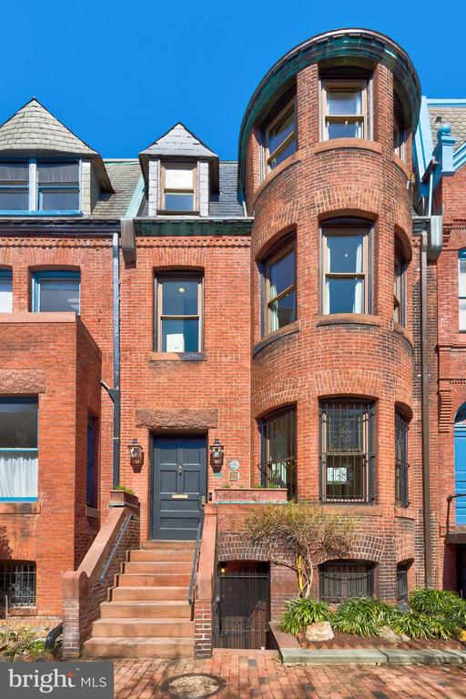 Featured in both The New York Times and Washingtonian last year, 1613 Riggs Place NW is a one-of-a-kind home worthy of all the buzz it gets. Set in the heart of DuPont over four exceptional levels, this stately row home combines character and luxury from one coveted address. Step beyond the elegant front doors to discover a home that embraces its past while remaining firmly rooted in the now. Inside, great care has been taken to preserve the home's authentic period details while fully updated high-efficiency systems deliver a truly 21st century living experience. The home's welcoming foyer leads to a bright and open living room complete with a fireplace and turret window, while the grand dining room is the ultimate backdrop for your next dinner party. Framed by French Doors that flood the space with light, the dining room offers an indoor/outdoor dining experience fit for every occasion. Around the corner, the gourmet chef's kitchen has been freshly renovated to include new cabinets, professional-grade stainless steel appliances, a brand new skylight, ample counter space, and heated flooring. Head upstairs to the inviting second floor, where an expansive Primary suite set over the entire level awaits. Some highlights? Be sure to check out the Primary Suite's large master bedroom, stunning library, spacious walk-in closet, and newly remodeled bathroom with heated flooring (to name just a few). The top floor includes three more bedrooms, all flooded with natural light, a bathroom with soaking tub, and a generous linen closet. Downstairs, the fully-finished lower level doubles as your elegant in-law suite thanks to its large en-suite bedroom, full kitchen, living/dining area, separate laundry, and bonus half-bath. And at a time when the demand for outdoor space couldn't be higher, this home exceeds even the loftiest expectations. Wander outside and be transported to an idyllic oasis—your private rear courtyard that's made for entertaining in all seasons. Designed with convenience in mind, the home's two-car garage makes getting around a breeze and rounds out this memorable offering. Tucked away on a quiet, tree-lined street in vibrant Dupont Circle, residents will find themselves at the center of it all, close to both the Red and Yellow Metro lines, as well as the city's most sought-after shopping, dining, and cultural destinations. With its convenient setting, 21st century amenities, and quintessential DC feel, there's no doubt that 1613 Riggs Place NW is an exceptional place to call home.