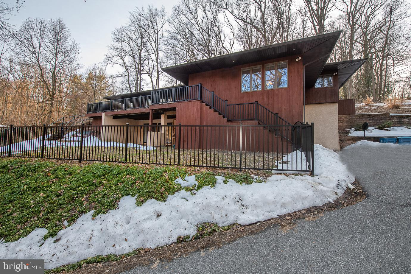This bi-level contemporary in Berwyn is a unique find and is beautiful inside and out! As you approach this home from the long, private driveway, you are greeted by clean architectural lines and warm tones of the wood-stained siding. A large foyer welcomes you home with hardwood floors and beautiful tile inserts. The hardwoods flow seamlessly throughout the first floor starting with the open kitchen and dining area that is surrounded by large windows where you can take in the sights of your beautiful wooded yard for a secluded escape. The kitchen is an entertainer's dream with beautiful white cabinets for lots of storage, upgraded granite countertops with plenty of space to cook your favorite dishes, stainless steel appliances, recessed lighting, tile backsplash and a large island finished with a wine fridge. Wait until you see the living room across the hall! Vaulted ceilings create distinguished lines and open space while skylights, sliding doors to your spacious deck and lots of windows bring in a ton of natural light to make this a bright place to cozy up next to a fire in your wood burning stove insert embraced by a beautiful stone facade. Take the stairs to the second level where the long hallway is illuminated by more skylights along the entire ceiling making this another unique feature of your home. The master bedroom has a walk-in closet, ceiling fan, sliding doors to a patio and an adjoining bathroom with double sink vanity and tile shower. Three more spacious bedrooms and a full bathroom with tub/shower complete the second floor. On your way down to the lower level, you will find a laundry room and powder room for your convenience. Additional space for a playroom, home office or movie night can be found in the finished lower level with a second wood burning fireplace, built-ins, sliding doors to the fenced in yard and interior access to the oversized 2 car garage and extra storage room. This home is located minutes from the Main Line, nearby parks and is 