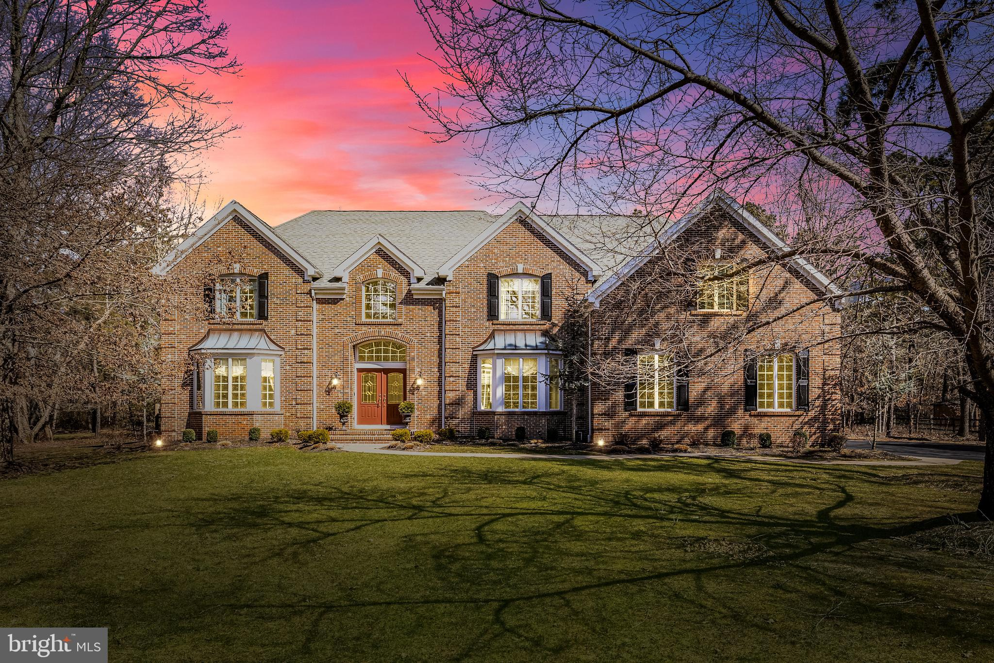 This fine Gary Gardner built executive home has everything going for it. The setting is exceptional, within prestigious enclave of Elderberry Cove.  This beauty is sited on almost 2 acres of wooded privacy, surrounded by extensive landscaping and manicured lawn areas, with an impressive approach from the street.  The deep setback allows for a long winding driveway leading to a side turned 3 car garage.  The Georgian styled brick front exudes a grand and welcoming style.  A meandering front walkway leads to a recessed double front door with Palladian window.  Multiple roof lines and quoined corners add interest and detail to the home.  The rear yard is enclosed by a split rail fence in perfect keeping with the natural setting.  This huge rear yard includes a custom hardscape patio and loads of space for you to extend the imagination into the outdoor living area of your dreams. There's already a large hot tub on the patio waiting for your enjoyment.  The interior of this 4BR, 2.5 bath home has al the amenities and fine finishes you'd expect in a home of this caliber.  Soaring and vaulted ceilings, lots of large and well -placed windows for a bright and warm environment, an extensive array of custom millwork including crown moldings, chair railings, wainscotings and window/door trims; hardwood flooring, plush pile carpeting and ceramic tile flooring throughout; designer paint and wall treatments with coordinating window dressings; stylish and grand light fixtures; skylights; peninsula styled Kitchen with cherry wood cabinetry, granite countertops, full appliance package; Breakfast Room with cabinet buffet counter; Family Room with floor to ceiling stone fireplace and wetbar; Sunroom with French Door entry; first floor Study; upper level balcony overlooks Foyer & Family Room; lavish Owner's ensuite with Sitting Room & abundant closet space including w/in closet; huge tiled bath with whirlpool tub, oversized his/her vanities, stall shower; 2 remaining large bedrooms plus