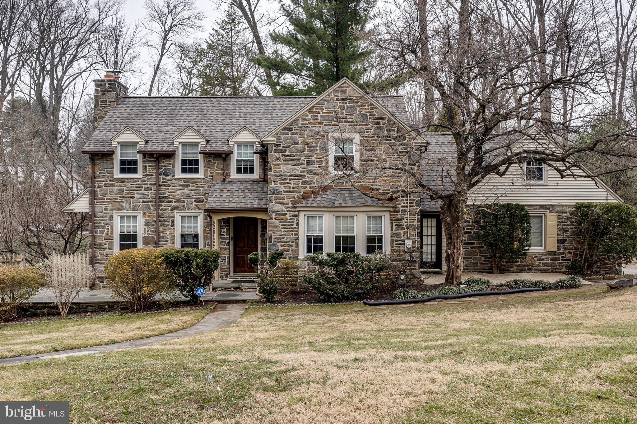 A private retreat in Penn Valley located on a quiet, tree-lined street. Enter into this classic stone Colonial renovated with a contemporary flair and be wowed with this modern and open floorplan. An inviting stone path leads you to this four-bedroom, four-and-a-half-bath stately home. Center hall foyer is open to the generously sized living room featuring a wood-burning fireplace and access to the screened-in three-season porch.   No detail was left behind while designing this brand new kitchen; featuring classic white shaker cabinetry, a free-standing island/breakfast bar for casual dining, quartz countertops, high-end stainless steel appliances, and a custom tiled backsplash. This kitchen is complete with a double-door pantry showcasing floor-to-ceiling shelves. Open to the kitchen is both the breakfast room and dining room which feature large bay windows, as well as the great room which includes a gas fireplace and wine refrigerator. A brand new powder room completes the first floor.  The second floor offers a spacious deck overlooking the grounds located at the top of the main staircase. The primary bedroom ensuite is highlighted by a large, spa-inspired bathroom with freestanding tub, oversized glass stall shower, double vanity, and expansive walk-in closet custom built-ins. Two additional bedrooms include generous closet space, with access to the full hall bathroom. The fourth bedroom features vaulted ceilings and an ensuite which would make a perfect fourth bedroom, in-law suite, or home office with access to the back stairwell. For convenience, there is a second-floor laundry room and a cedar closet.   The walkout lower level of this home has beautiful wood-like flooring throughout and features an additional recreation room, full bathroom, an abundance of storage space, providing the potential for an additional bedroom or home office. An additional outdoor entertaining patio and built-in stone fire pit can be accessed from the sliding doors.  Situated in th