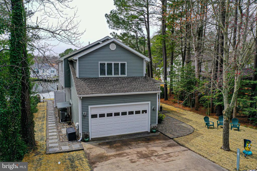 Don't miss out on this beautifully updated waterfront home in the Teal Bay section of Ocean Pines.   Since 2015 the sellers have completed the following updates; new roof and siding, HVAC replaced ('18),  interior and exterior doors, hardwood flooring on 1st floor, total kitchen remodel with high end finishes, paint throughout, boat lift and composite dock as well as outdoor shower and screen porch redo ('19).   The first floor offers an open floor plan for kitchen/living/dining rooms that flows to outdoor living space overlooking the canal, as well as bedroom, guest bath, and laundry room.   Master suite, 2 spacious guest bedrooms and full bath on 2nd floor.  The home is centrally located in amenity rich Ocean Pines, close to the Yacht Club w/ restaurant, bar & marina, White Horse Park - the location of weekly farmers market and other events, Community Center and pools.  This move-in-ready home is updated, well cared for, tastefully decorated AND sold partially furnished.