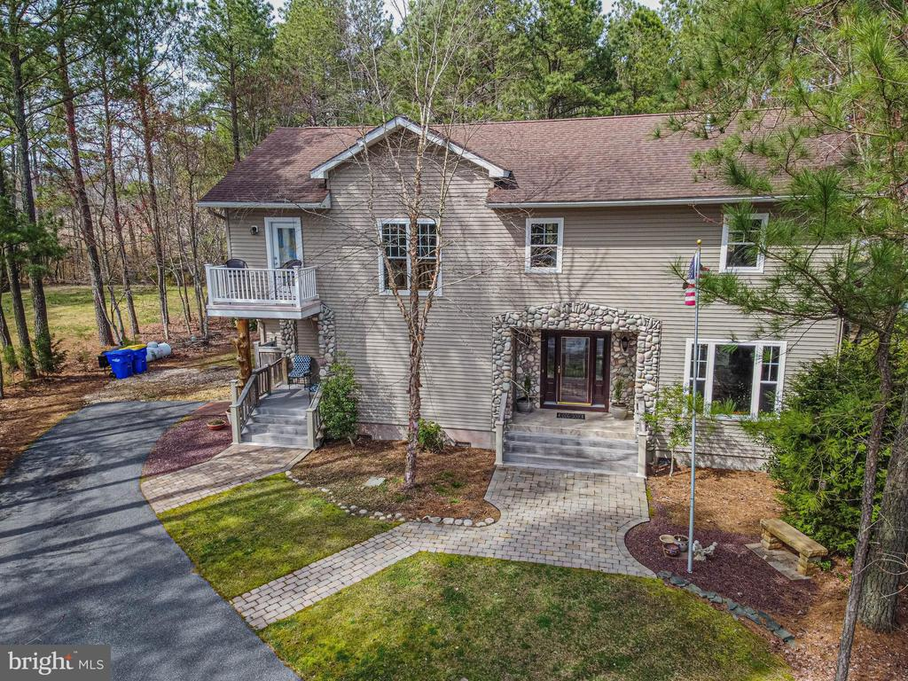 Upon pulling up to this beautiful custom built home, you will see immediately what makes this home stand out in the crowd!  Located in the neighborhood of Bayview Estates, this home has not only a large wooded lot, but also a boat ramp and community pool.  The custom STONE on the outside and inside along with the finishes throughout the home along with it's spacious areas for large family gatherings throughout the year are an additional bonus.  If you are a cook, you will love this spacious kitchen with high end appliances and plenty of work/counter space.  Site plan shows area for future garage, that can be built.