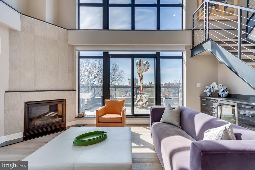 Corner Penthouse in Q14 | 2 Beds | 1 Lofted Den | 2.5 Baths | 1,700 Sf | 800 Sf Wrap-Around Terrace | 2 Separately Deeded Garage Spaces | Building: Built in 2006, 28 Residential Units & 2 Commercial Unit, Common Rooftop Deck, Party Room w/ Outdoor Terrace, Extra Storage | Unit: 19 Ft. Ceilings, Wrap Around Terrace w/ Irrigation System & Custom Lighting, 90 Linear Ft. of Windows w/ South Western Exposures, Hunter Douglas Silhouettes & black-out Automated Shades, Custom Lighting w/ Lutron Maestro Dimmers, 2 Bedrooms w/ En-Suite Baths & Balconies, Boffi Custom Built-In Closet w/ Accent Lighting in Primary Suite, Fully Integrated Indoor & Outdoor A/V System by ABE Networks, Gas Fireplace w/ Ann Sacks Tile Mantle, Wet Bar w/ Beverage Cooler & Storage, New Energy Efficient HVAC System, Nest Thermostat, New White Oak Wide Plank Hardwood Flooring, Laundry Room w/ Miele Washer & Dryer, Powder Room w/ Linen Closet on Main Floor | Kitchen: White Oak Cabinets w/ Custom Wine Storage Designed by Jennifer Gilmer, Italian Glass Tile Backsplash, Italian Granite Countertops, Stainless Steel Appliances, Viking Gas Range & Wolf Exhaust Hood, Sub-Zero Refrigerator, Bosch Dishwasher, Insinkerator Disposal, Large Format Slate Tile Flooring | Bath: Each Bathroom is Custom Designed w/ Designer Lighting Fixtures & Finishes, Floating Vanities w/ Storage, Custom Wallpaper Accent Walls Throughout, Double Vanity w/ Quartz Countertop in Primary Suite, Dual Shower Heads & Custom Niches, White Subway Tile Backsplash & Porcelain Tile Flooring, Mirrored Medicine Cabinets, Frameless Glass Shower in Primary Bath, Kohler Fixtures