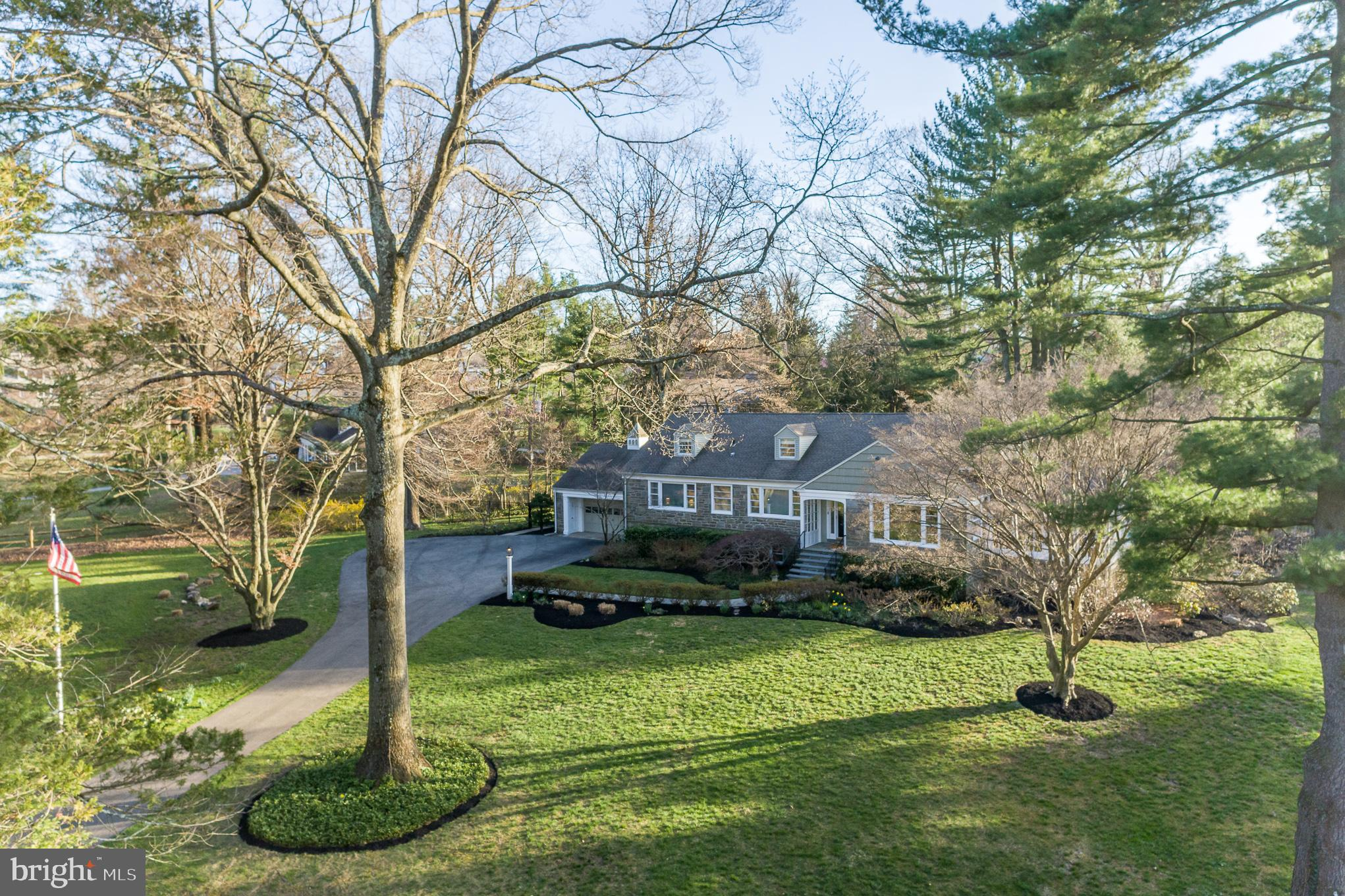 Nestled in the heart of coveted Northside Wynnewood, this picturesque home by Mahoney builders is a stunner!  This 5 bedroom, 3 full/1 half bath stone Cape Cod rests on a .95 acre of sprawling landscaped grounds with spectacular plantings! With over 4,000 square feet, 316 McClenaghan Mill Road boasts generous indoor and outdoor living spaces. The extended driveway to the home adds extra flair to its fabulous curb appeal! From the beautifully pointed hardscaped walkway, you will enter 316 McClenaghan Mill and fall in love!   Beautiful refinished oak hardwood floors run throughout the first floor from the center hall to the large formal living room. Equipped with a gorgeous wood burning fireplace and the finest moldings, the living room flows directly into the formal sunlit dining room. Additionally, directly off the living room is a seasonal light filled porch with full glass windows that can be replaced with screens during the warmer months.   The back of the home meets the needs of everyday living and is a true haven for entertaining! The space includes a large, eat in kitchen with two toned custom cabinetry, a cherry island with a butcher block top, neutral granite countertops, tile backsplash, a butlers pantry with sink, and abundant storage.  Directly off the kitchen is an enormous family room which features custom built-in cabinetry, a beautifully pointed stone wood burning fireplace, custom Anderson windows and doors, vaulted ceilings and skylights. Open the double doors directly out to the tiered deck and there lies your very own private backyard oasis completely fenced in – absolutely perfect for summer nights!   The main floor also has a large serene first floor master, with great closet space. The ensuite master bath includes an oversized shower with a custom glass door, a porcelain tile floor that extends to the shower walls, and a white wood double vanity with Carrara marble countertops! There are two additional bedrooms and a full hall bath on the first