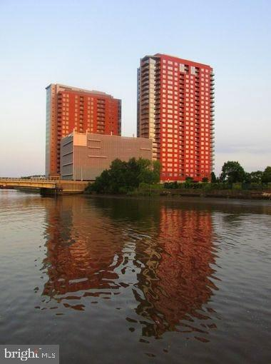 """This 2-bedroom, 2 full bath condominium PLUS DEN is situated in Wilmington's premier luxury waterfront high-rise. Located within walking distance to Amtrak, many downtown employers, Wilmington river front attractions & easy access to I-95, this condominium features 24/7 concierge doorman, covered parking with 2 deeded parking spaces, 24-hour fitness center, rooftop deck with saltwater swimming pool & Jacuzzi with panoramic views of Wilmington.  This unit features an open floor plan, 9 ft. ceilings & sweeping views of the river, boardwalk & downtown Wilmington from every room. Upon entering, you are greeted by hardwood floors that flow throughout the living room, dining room & kitchen. The spacious living room features floor-to-ceiling windows leading to the balcony where you can enjoy local rowing competitions by day & beautiful firework displays by night. The kitchen is equipped with 42"""" cabinets, granite counter tops, stainless steel appliances, a handcrafted butcher block storage area & a breakfast bar overlooking the living room.  The first bedroom features a fabulous view of the river, provides an oversized closet & is adjacent to the first full bath that hosts a tub shower.  At the opposite end of the unit, you will find the second bedroom with double closets & access to a private luxury 4-piece bathroom featuring tile flooring, an over-sized walk-in shower with white subway tile, separate soaking tub, & double vanity.  The den, which could be utilized as a third bedroom, office, or additional storage is also located on this side of the unit making for additional privacy for house guests or roommates.  The unit also features in-unit washer/dryer & storage closets. The monthly condo fee covers water, sewer, trash, hot water, common area maintenance, building insurance & a community room equipped TVs & a full kitchen. Come see this move-in ready unit & call it HOME today! Please contact Melissa Ellis for all inquiries!"""