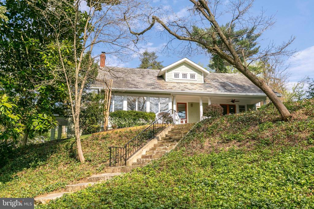 """Perched atop one of the highest points in Round Bay, surrounded by nature, is this charming 1930's renovated home. The 3 Bedroom / 3 Full Bath cedar shingled Cape Cod  bungalow is full of rustic charm and unique, timeless architecture! Welcoming you to the property is an unforgettable flagstone staircase leading to the entrance of the home from its lower parking area. From the front veranda and Great Room, the three-season water view is simply beautiful and the sunsets awe inspiring! A rare find with heart pine flooring and high ceilings throughout, main level full bath and den. An abundance of windows and natural light provide a """"tree house"""" feel with hilltop views of nature. The kitchen includes a benched dining area with a large bay window for a sunny start to the day. With crisp white cabinetry and sleek black countertops, it leads to an outdoor back terrace for year-round grilling! A full unfinished basement offers lots of storage, outside exit plus built-in work bench. The  double lot is  .82 acres, providing privacy and nature!  The property includes three parking areas which provides space for a family of vehicles, boat, trailer or other recreational equipment. The large lot provides the possibility for an expanded lawn, garage, addition or pool. PUBLIC water, sewer and gas! Convenient to 3 neighborhood beaches, the B&A bike trail, Baltimore, Washington, DC, and BWI Airport. """"Blue Ribbon"""" schools, nearby shopping and restaurants make the location truly perfect! All this in a premier water-privileged community, Round Bay, which offers an incredible sense of community, 3 private neighborhood beaches – with piers and boat slips – pavilions, playground, tennis courts and more! AAC sq footage is NOT correct"""