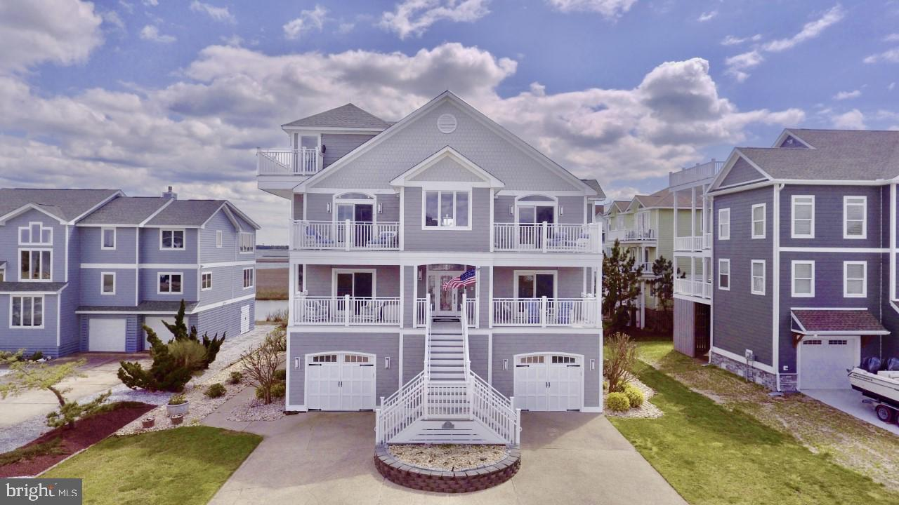 Gorgeous coastal home in the prestigious gated community of South Shores. Enjoy the sunrises and sunsets from this luxurious well-designed home with numerous decks and balconies from almost every room allowing you to fully enjoy this unique and desirable location overlooking the bay and Indian River Inlet Bridge.  This beautiful property was prominently featured on the famous Beach & Bay Cottage Tour!  The spacious great room invites you to linger, showcasing a lovely gas fireplace, soaring ceilings, rich mahogany plank floors and expansive windows allowing for wonderful natural light. This amazing open floor concept flows seamlessly into a gourmet kitchen featuring a grand granite island with overhead pendant lights, stainless steel Thermador professional grade appliances, double ovens and a dining area that will accommodate a large group of friends and family.  Delight in the panoramic bay views in the cozy sunroom complete with natural beadboard millwork and heated tile flooring to keep you warm in the cooler months.  At the end of the day, relax and unwind in the primary bedroom en-suite boasting a separate room for an office or sitting area, a walk-in closet and en-suite bath with dual sink vanity, soaking tub and tiled stall shower.  Transition downstairs to the main level via elevator or staircase to four additional bedrooms, two en-suite, and another family room area with access to the lower level covered wrap-around patio that provides shade for a comfortable experience on a hot day.  There is a bonus room on the third level, a mud room on the lower level with access to an oversized two car garage with an abundance of storage space for your beach gear and watersports equipment!  After a day at the beach, use the outside showers to wash away the surf & sand.   It just doesn't get any better than this!  South Shores is an amenity rich community offering a swimming pool, tennis and pickleball courts.   Revel in being just a short distance to the ocean and bay 