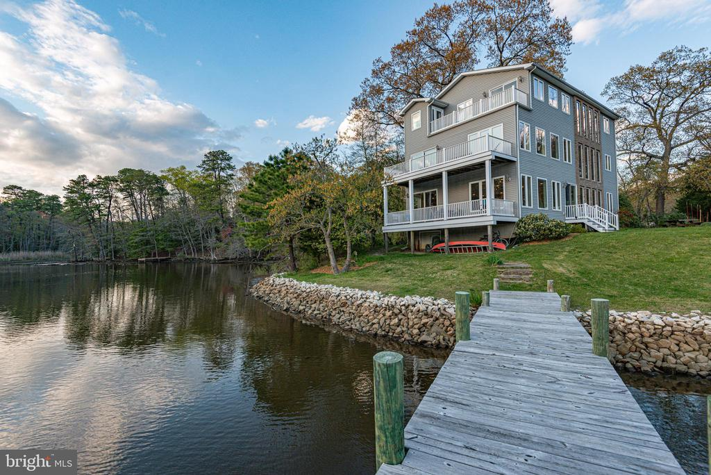 Completely Custom 3.30-acre waterfront property with pier and 235 feet on secluded Black Hole Creek.  Stunning water views from every room.  The home has 5 bedrooms and 4 and 1/2 baths with decks on all 3 levels.  The foyer invites you into this amazing 3 story staircase leading to 12 water view windows with beveled prairie grids.  The first floor offers an office or in-law suite; with a full hall bath.  The great room features a large fireplace, gourmet kitchen and open dining space.  The kitchen has custom cabinets, granite counter tops, and island cooktop. Adjoining pantry with tons of storage space.  Enjoy the water view as you ascend the steps to the second floor. Open floor plan with refrigerator, dish washer, counter and sink for entertaining on the second level.  Jack and Jill bathroom with double sink has direct access to one bedroom.  Second bedroom has both a pond and creek view.  Third floor includes two-bedroom suites with Juliet balconies overlooking foyer.  The master bedroom features a jacuzzi tub with fantastic water view and door to the deck.  Master bath has separate toilet and shower room with window and tiled shower seat.   Beautiful unique mostly wooded property with large pond.  Wildlife abounds, great area for bird watching, walking and bike riding.  30 minutes to Baltimore, 45 minutes to Washington, and a half hour boat ride to Annapolis.  No flood insurance required!!