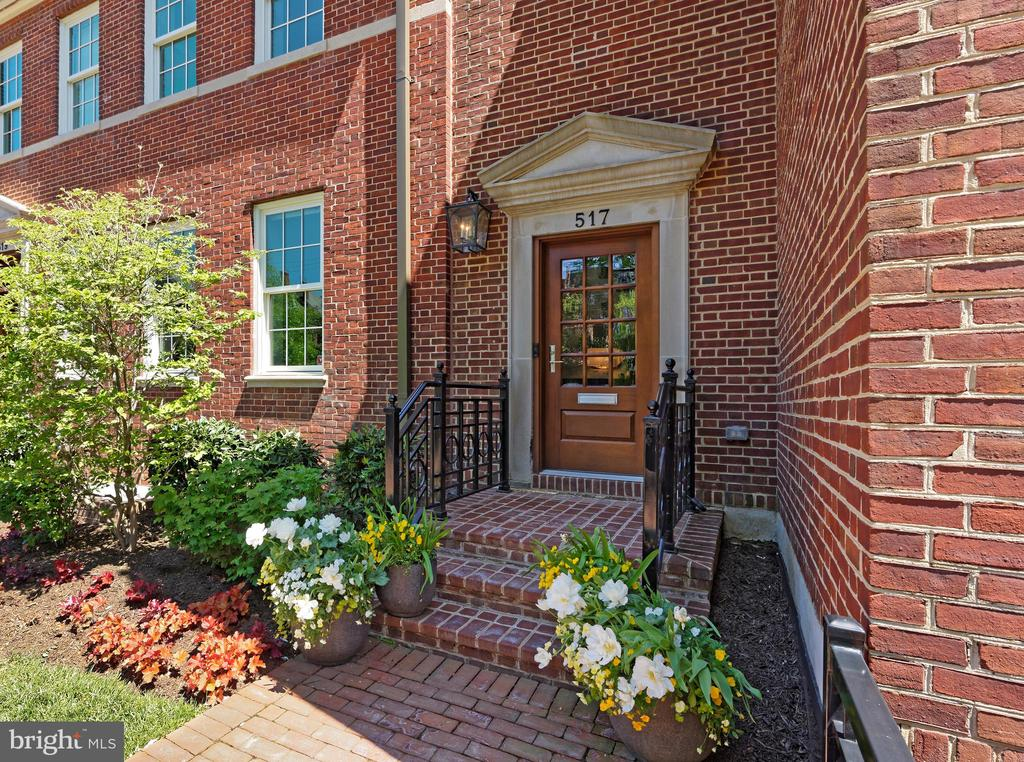 A historic brick building modernized to perfection is now available for your viewing pleasure at 517 N. Saint Asaph Street in Old Town!  This impeccable 3-story single-family residence has all the style and luxuries you could want in a new high-end home, from an elevator accessing all levels to a detached 2-car garage with EV outlet, storage, and studio with full bath above. A lovely landscaped fenced front yard and brick walkway optimize charm and curb appeal, while inside is sleek and stunning with an open floorplan and contemporary flair.  A dramatic entrance graced by an artful staircase greets your arrival, accented by an exquisite Timothy Oulton chandelier featuring crystals with metal rods creating a dazzling rainfall effect. The large, beautiful living room with a striking 2-sided gas fireplace sets an inviting tone for entertaining, with easy open dining for the host. Elegant wide-plank walnut floors enrich the ambience, and designer recessed lighting sparkles above. The chef's kitchen is a real showstopper, finely appointed with generous Snaidero Italian cabinetry, quartz countertops, premium stainless steel appliances by Thermador, and wine cooler for favorite vintages.   Open to the kitchen is a sun-bathed breakfast area brightened by a wall of windows and fabulous family room that shares the gas fireplace. Glass doors open to the rare, extraordinary, expansive private fenced rear terrace for the ultimate outdoor living, affording plenty of lounging/sitting and dining space. An alfresco outdoor kitchen with Urban Bonfire Canadian cabinetry, gas fire pit, tasteful lighting, and lushly planted oversized flower pots with rain gauges and irrigation heighten the experience. Inviting, well-proportioned bedrooms provide a comfortable place to land, offering walk-in closets and immaculate en-suite baths. The divine primary suite bath has upscale Waterworks fixtures, marble floors, a dual-sink vanity, spa shower, and freestanding soaking tub for unwinding. Other 