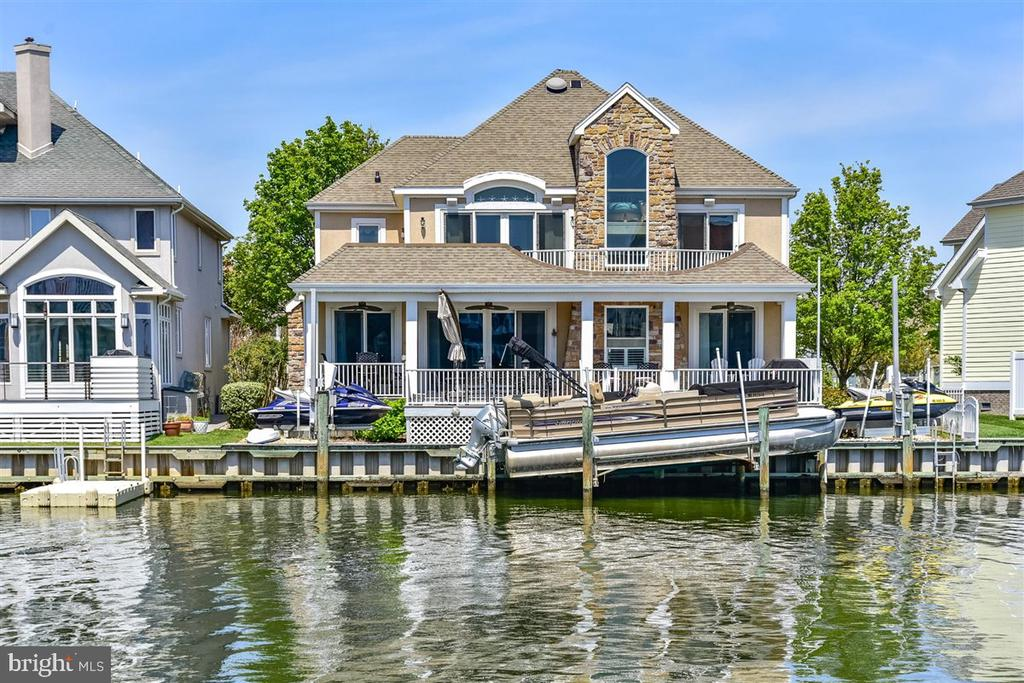 Magnificent luxurious custom 4BR/4.5BA direct waterfront home in Heron Harbour Isle has just been listed!   This home is stunning with spectacular canal and Bay views and desirable southern exposure.  There is a boat slip with  lift and two jet ski lifts for all your water toys.  From the minute you walk in the front door you will fall in love with this home. There is a large family room with a gas fireplace for year around enjoyment.  The dining area flows off the family room and kitchen.  The kitchen has a large breakfast bar, Corian countertops and plenty of cabinet space.  The first floor also has a guest suite with full bath and your guest will be delighted with the view of the Ocean City skyline lit up at night.  There is also a laundry room and pantry on the first level that lead to the oversized garage.  On the second floor there is a spacious master suite overlooking the water with a large walk in closet and full bath with jacuzzi tub and shower.  The master has a glass slider leading to the deck to watch sunsets.  There are two more bedrooms on this level and each has its own private bath and oversize walk-in closet.  The outdoor space is incredible and the perfect space to entertain family and friends.  Relax in one of the lounge chairs and soak in the sun or sit under the covered deck and read a book in the shade. Enjoy a crab feast or barbeque on the large deck overlooking the water. There's kayaking and paddle boarding for some quiet time on the Bay, and jet skiing and motor boating when high powered watersports are calling your name.  This home is in the amenity rich community of Heron Harbour. The community amenities include an indoor heated pool, outdoor family pool, Olympic size lap pool, kiddie pool, fitness center, library, social room and two lighted clay tennis courts. This is more than a luxurious home, it's a wonderful lifestyle.