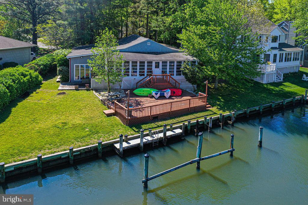 Beautiful large waterfront lot overlooks intersecting canals, and also offers river views!  Just a short distance to the open bay.  The extra large three season sunroom opens onto the spacious rear deck.  This house is much roomier than it appears from the outside.!  Enjoy the wide open living area taking advantage of the views. The lower level features a den/office and a utility room/workshop combo. Host gatherings and watch the wildfowl from the grassy, cleared side yard before launching your boat from your private dock!