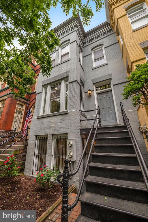 NEW LISTING! Located at the crossroads of the perennially popular neighborhoods of Logan Circle and Shaw, yet tucked on a quiet, one-way residential street, this lovely Victorian-style rowhouse offers the best of city living with the all the comforts and conveniences of a modern single-family home.  Featuring three generously sized bedrooms and three full baths, the home has beautiful appointments throughout such as crown moldings, hardwood floors, a wood-burning fireplace, double pane windows and high ceilings.  Spread over three levels, the property has been thoughtfully updated and boasts an oversized kitchen featuring granite countertops and stainless steel appliances, including an induction range, as well as an eat-in breakfast nook and large island. A covered rear deck overlooks the spacious brick patio and garden area, perfect for outdoor dining and entertaining.  Additional features include secure, off street parking for up to two cars and additional outdoor storage.